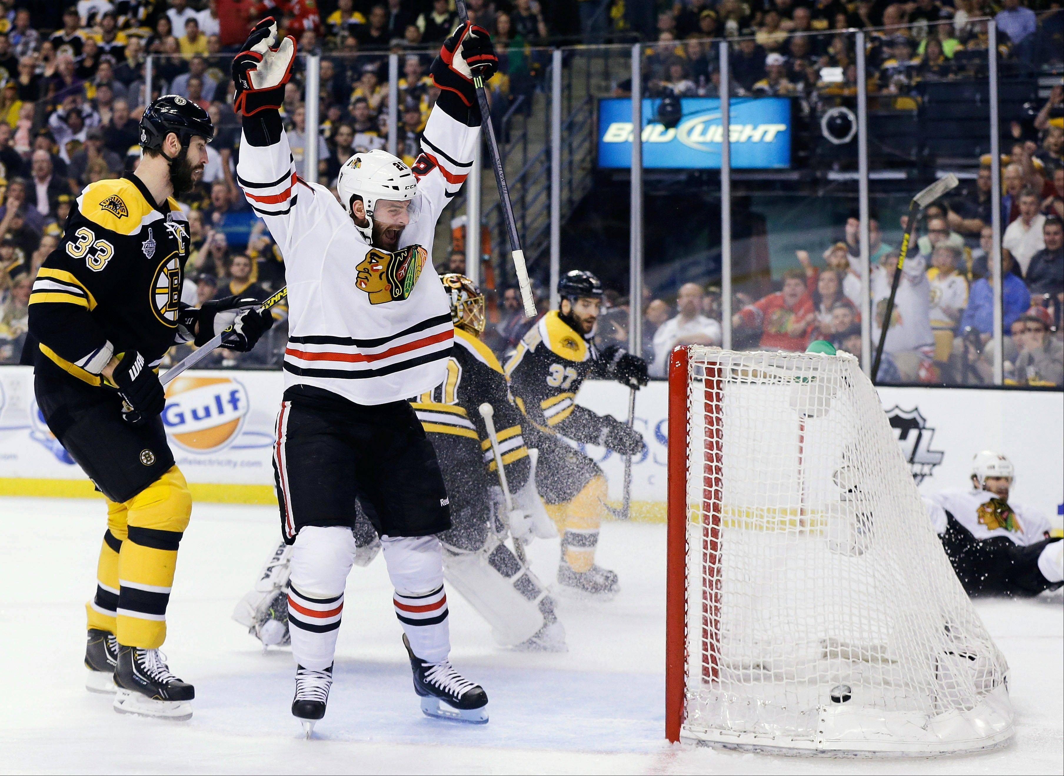Blackhawks left wing Brandon Saad, center, celebrates a goal by Blackhawks center Michal Handzus, right, in front of Boston Bruins defenseman Zdeno Chara (33) during the first period last night in Boston. Five other Blackhawks scored in the overtime Game 4 win.