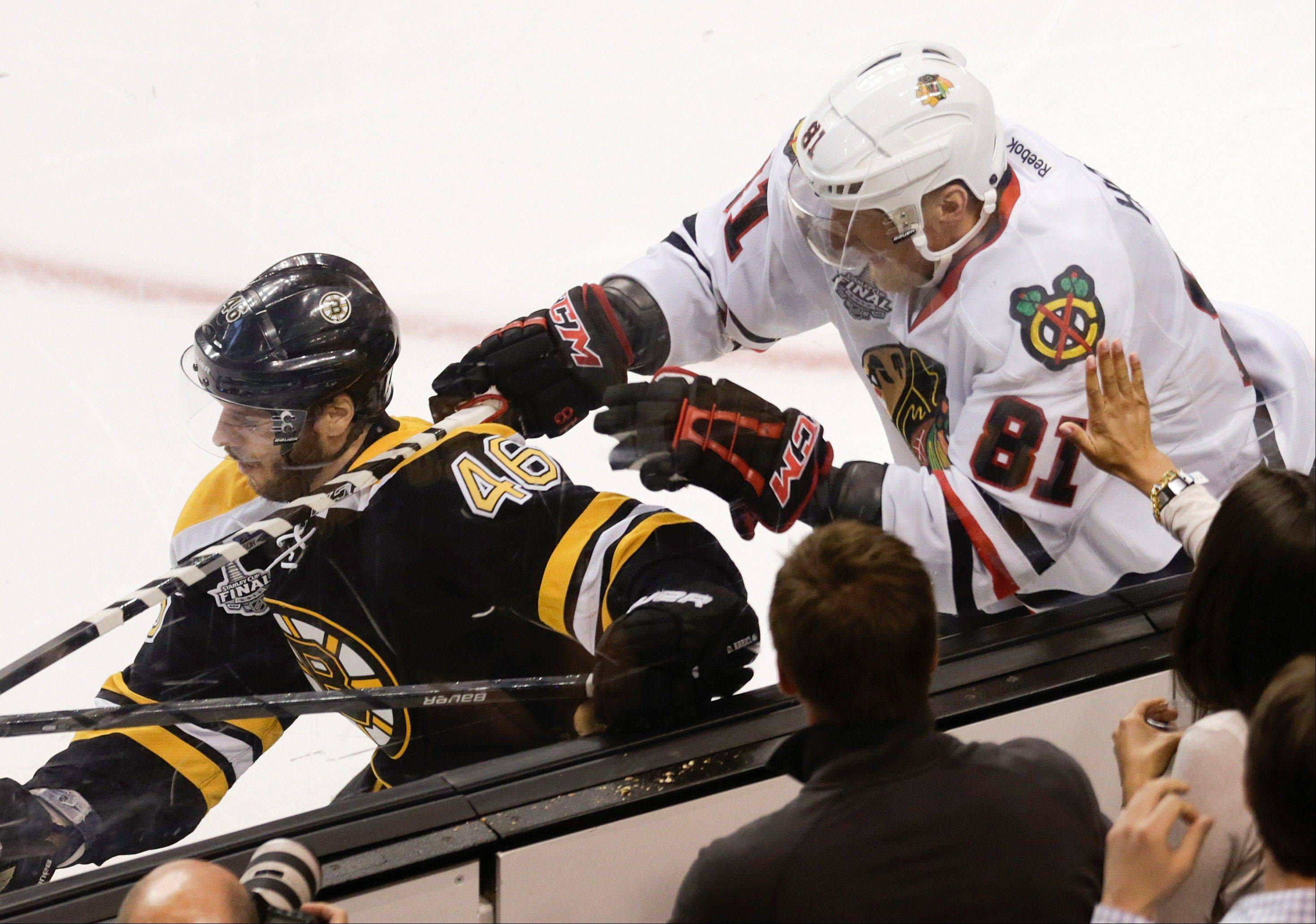 The Blackhawks� Marian Hossa checks Boston�s David Krejci during the second period in Game 4 of the Stanley Cup Final on Wednesday.