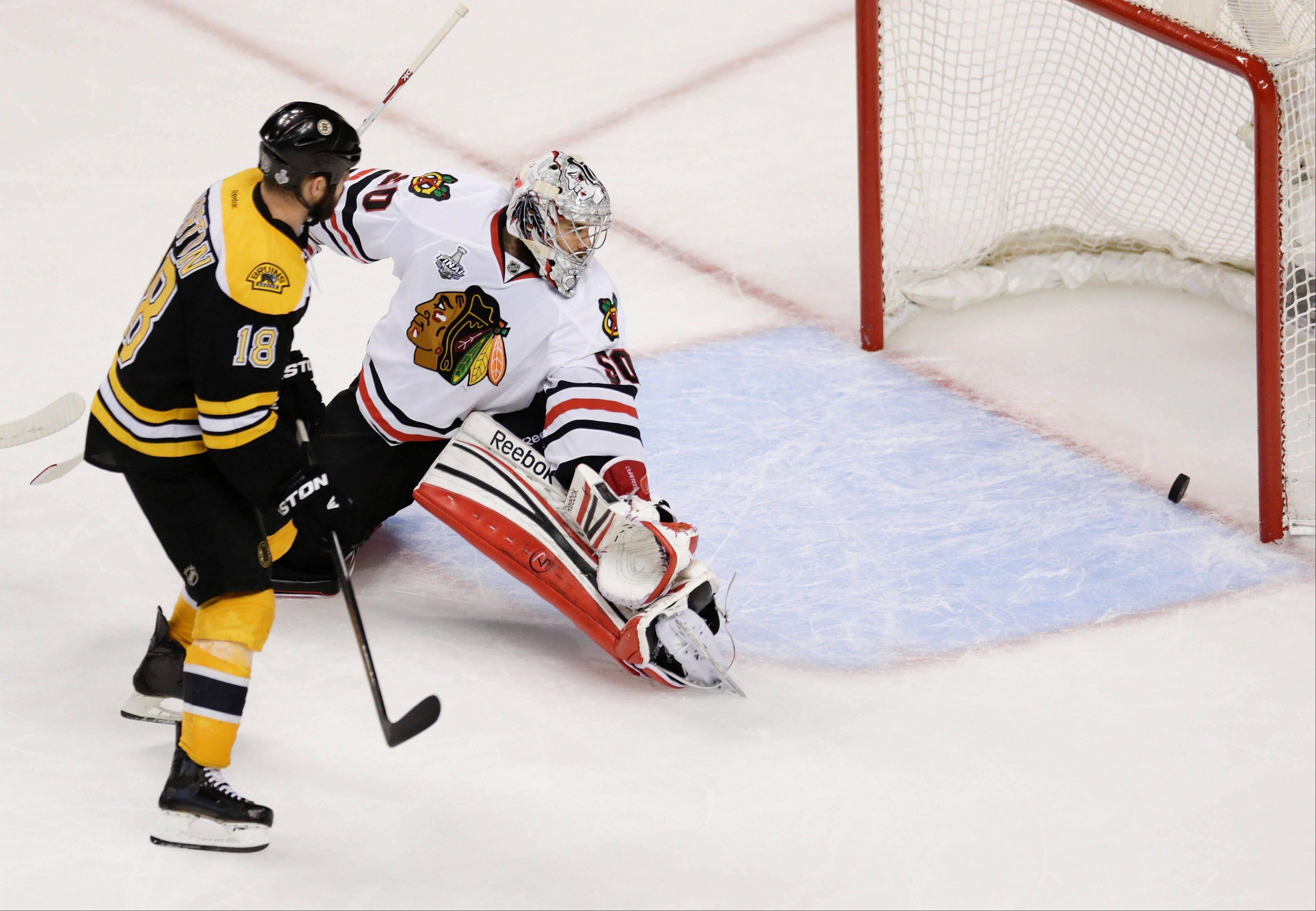 Boston Bruins' right wing Nathan Horton watches defenseman Johnny Boychuk's goal against goalie Corey Crawford during the third period in Game 4 of the NHL hockey Stanley Cup Finals Wednesday. The Bruins seemingly exposed a weakness in Crawford's game as all 5 goals he gave up were to the high side of his glove.