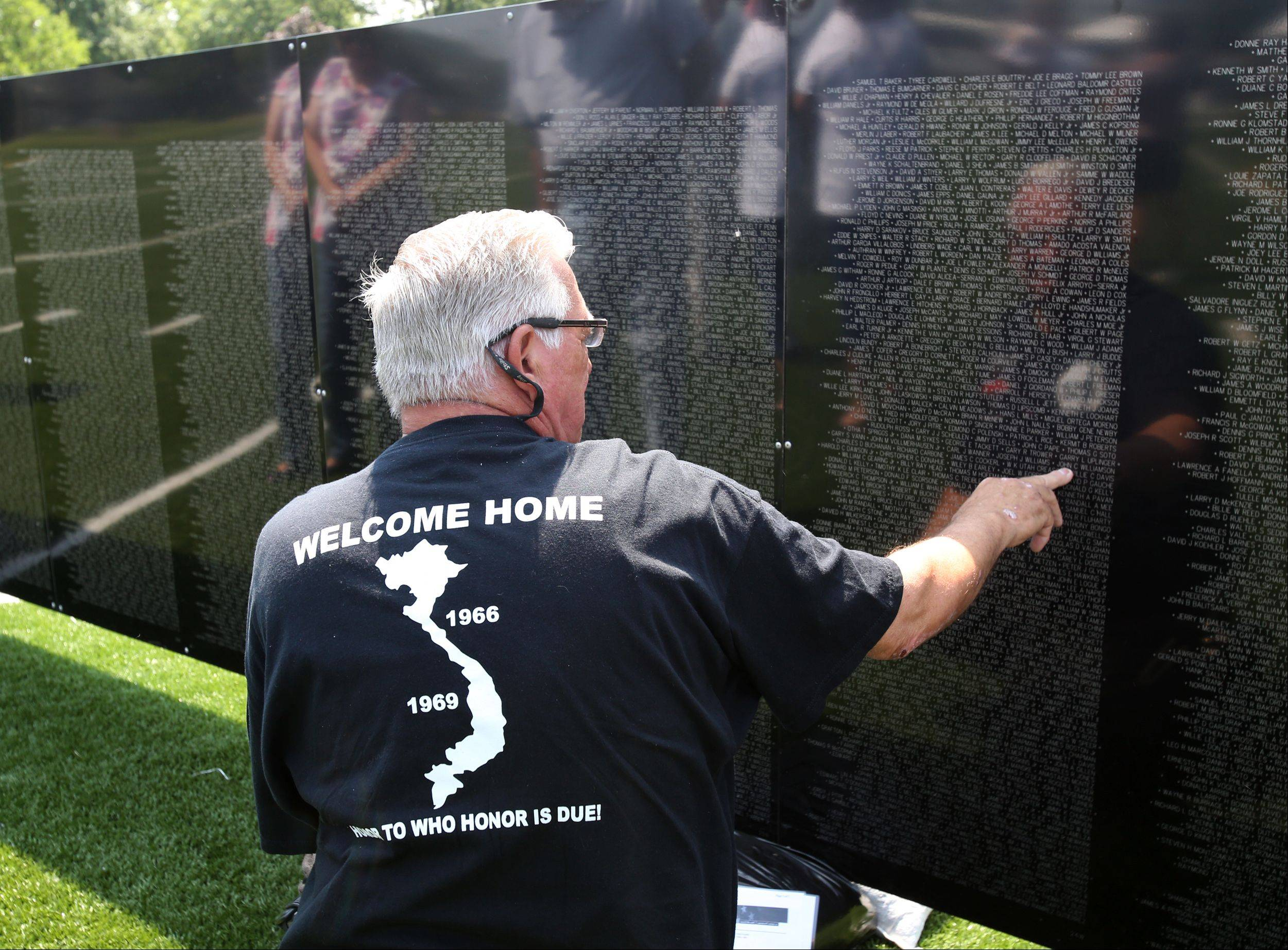 Helmut Stankevicius of Elmhurst, a veteran of the Army's 9th Division, pays his respects Thursday at The Wall That Heals, a traveling replica of the Vietnam Veterans Memorial Wall. The replica is on display in Bensenville's Redmond Park through Sunday.
