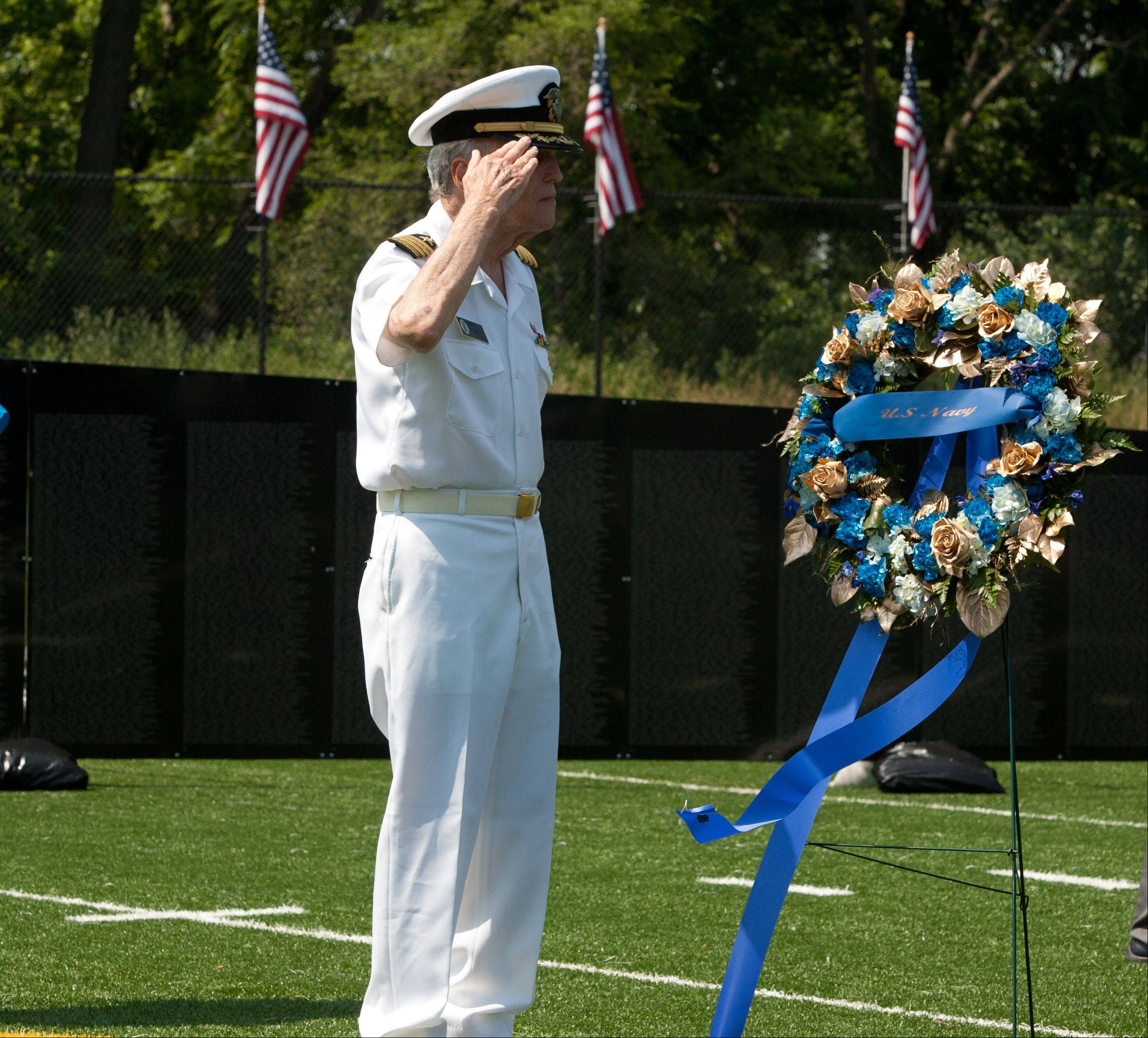 Navy veteran Alex Martella of Bensenville honors the fallen during opening ceremonies Thursday for The Wall That Heals, a traveling replica of the Vietnam Veterans Memorial Wall.