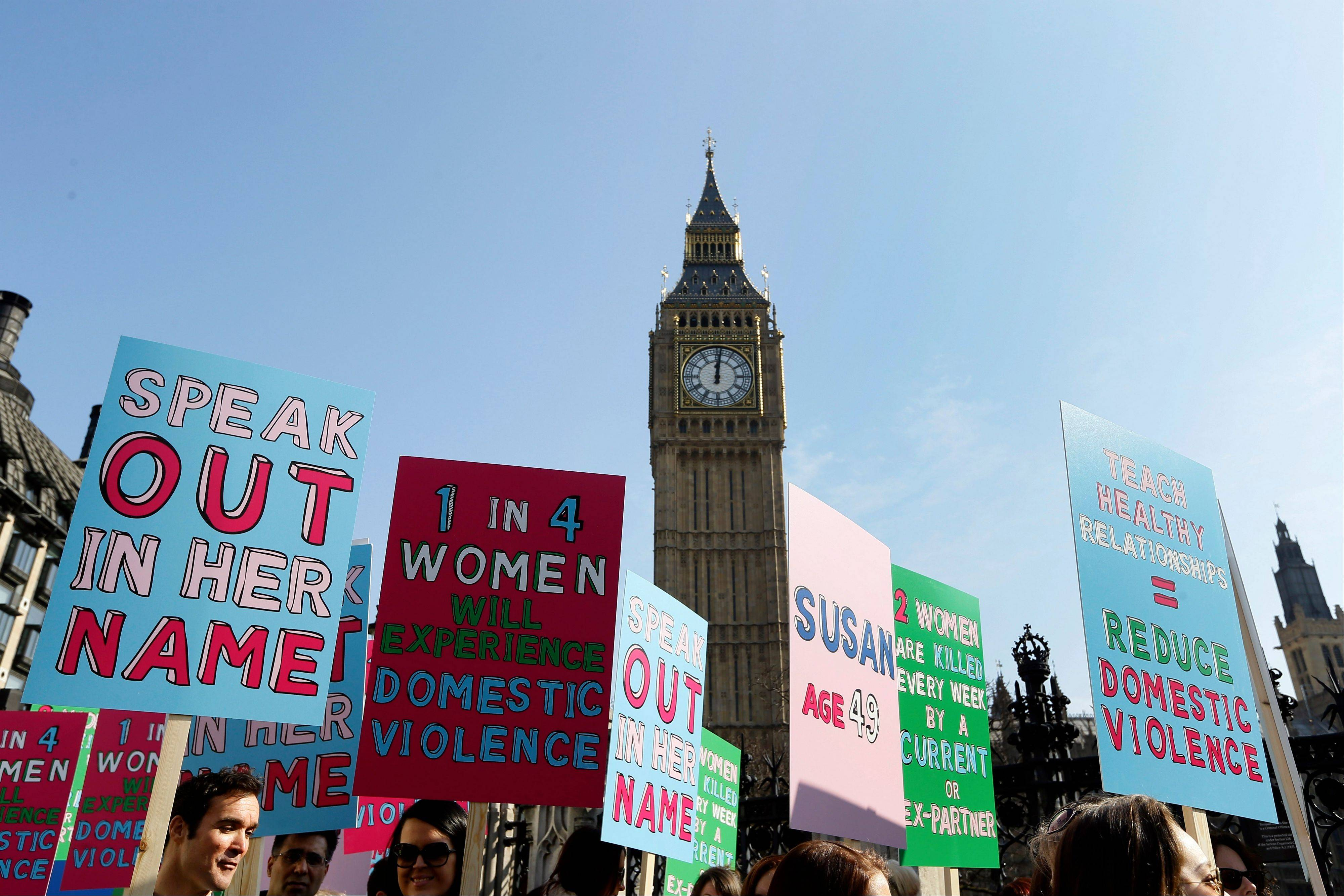 People hold banners during a demonstration against domestic violence near Big Ben in London, in the lead up to International Women's Day. About a third of women worldwide have been physically or sexually assaulted by a former or current partner, according to the first major review of violence against women.