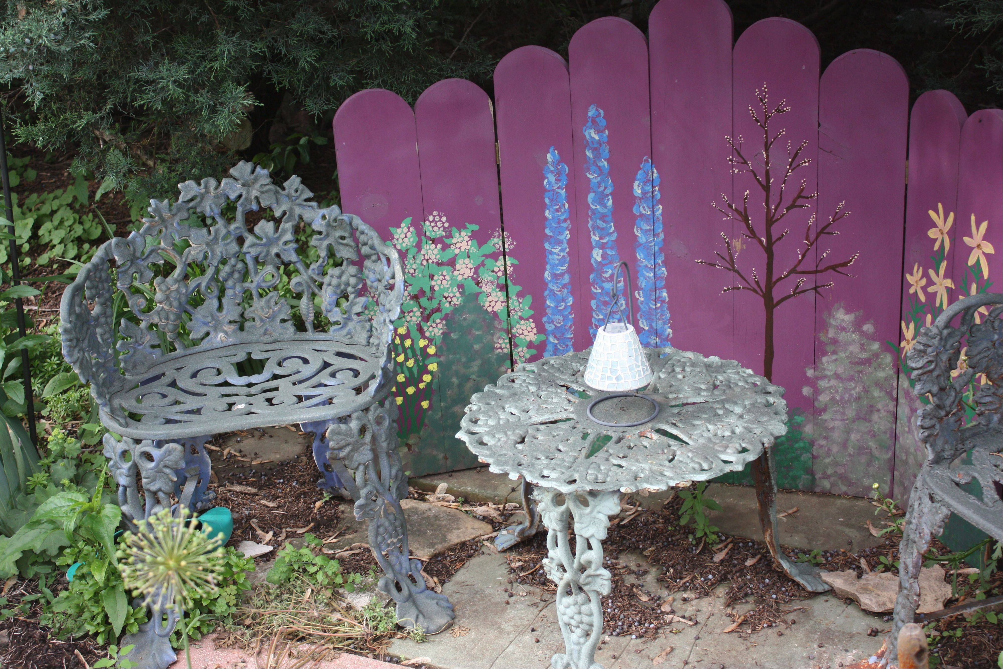 A floral painted screen that frames two metal patio chairs and a table is an inviting place to enjoy the Buehler garden.