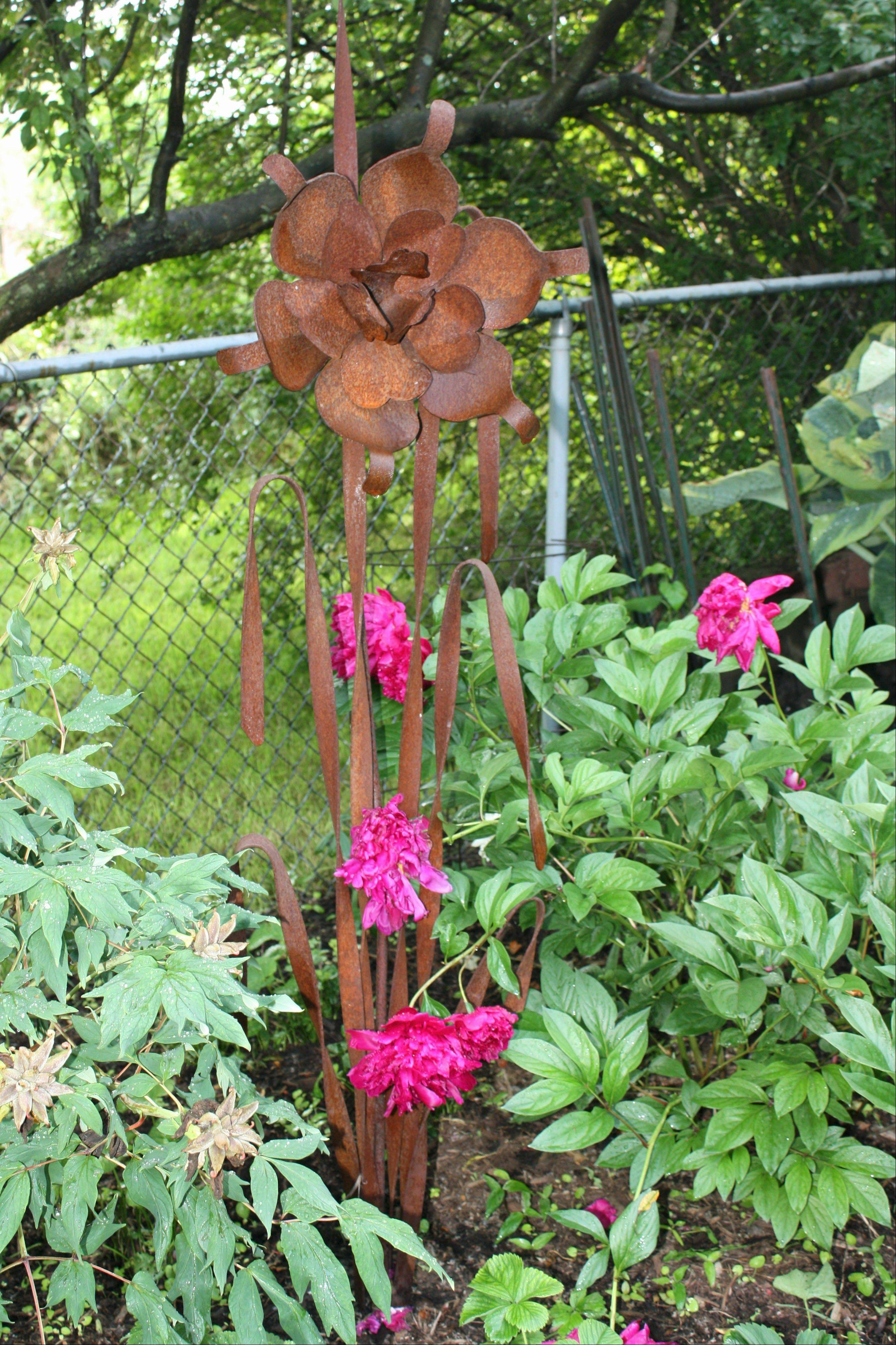 The metal sculpture in the Cebulski garden is a sample of a growing trend to add artistic enhancements to a garden.