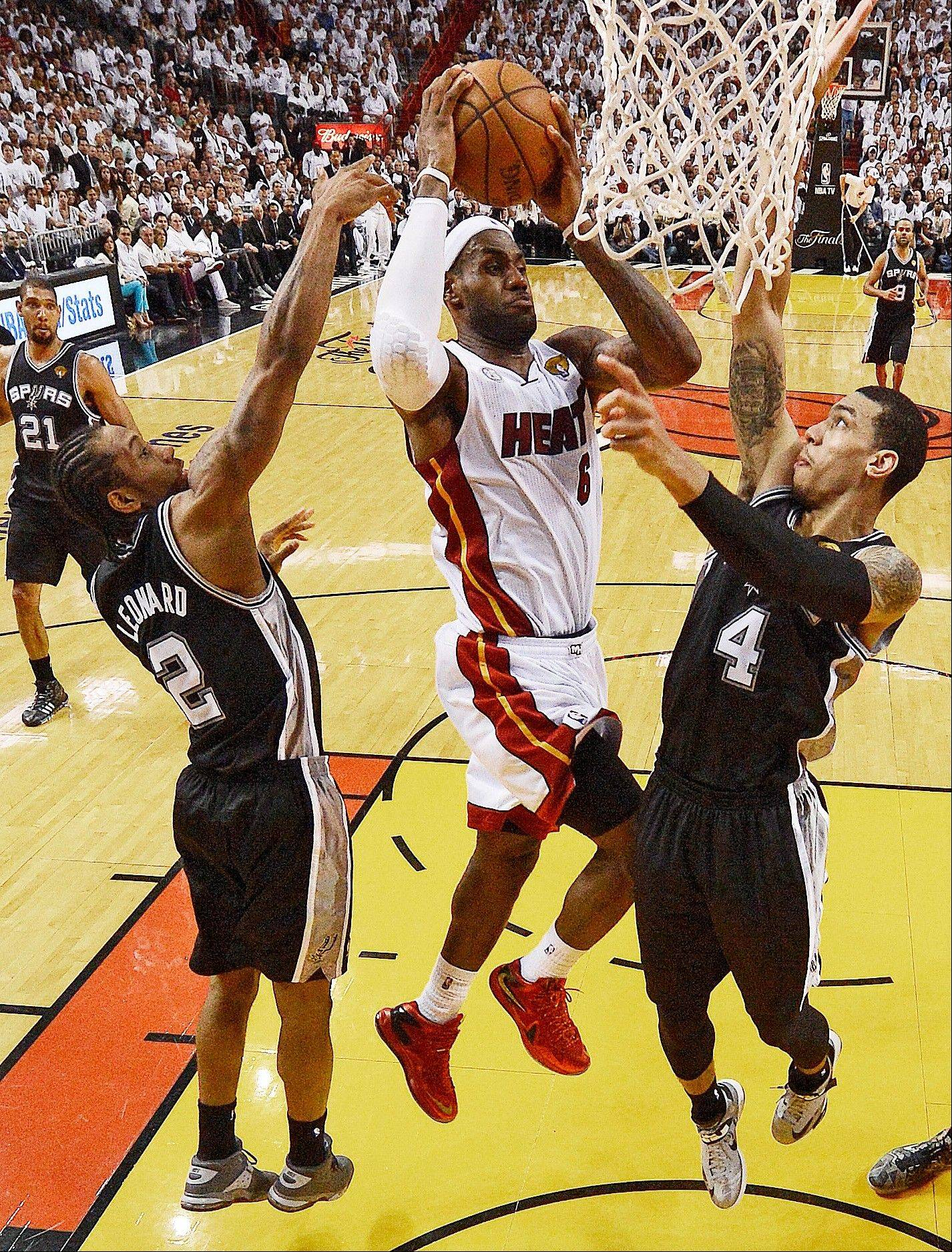 The Miami Heat's LeBron James (6) shoots against San Antonio Spurs' Kawhi Leonard (2) and Danny Green (4) during the first half of Game 7.
