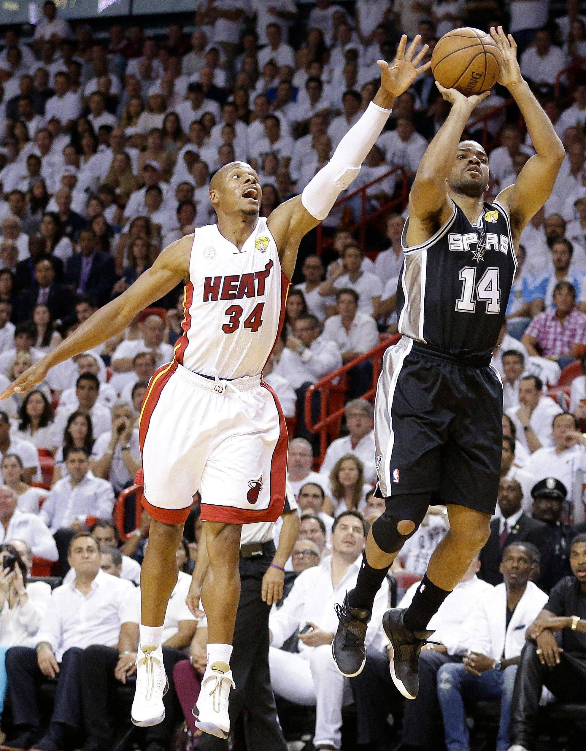The San Antonio Spurs' Gary Neal shoots as the Miami Heat's Ray Allen defends during the first half.