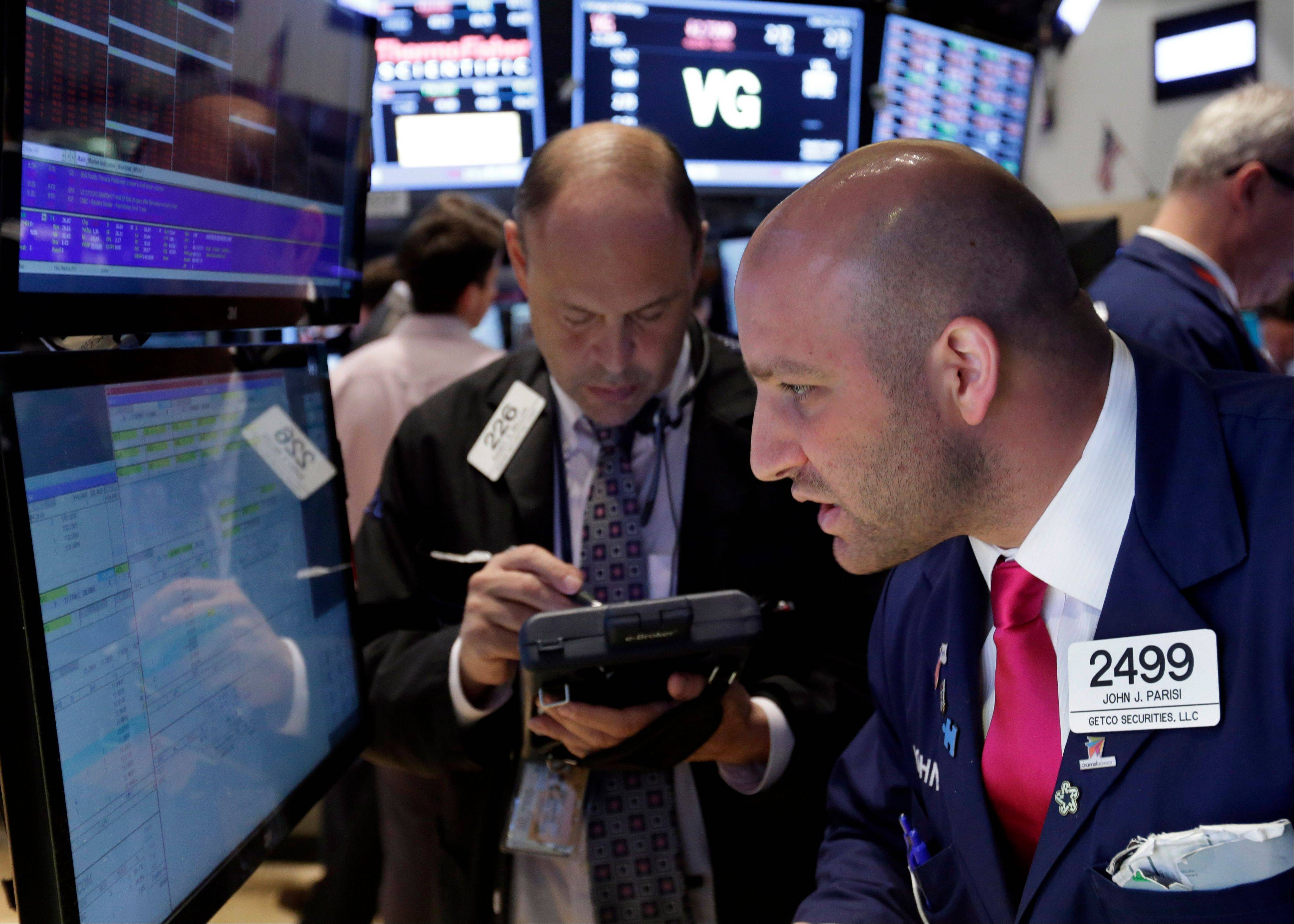 Specialist John Parisi, right, works with traders on the floor of the New York Stock Exchange. U.S. stocks rose in morning trading on Friday as traders regrouped following the biggest drop of the year.