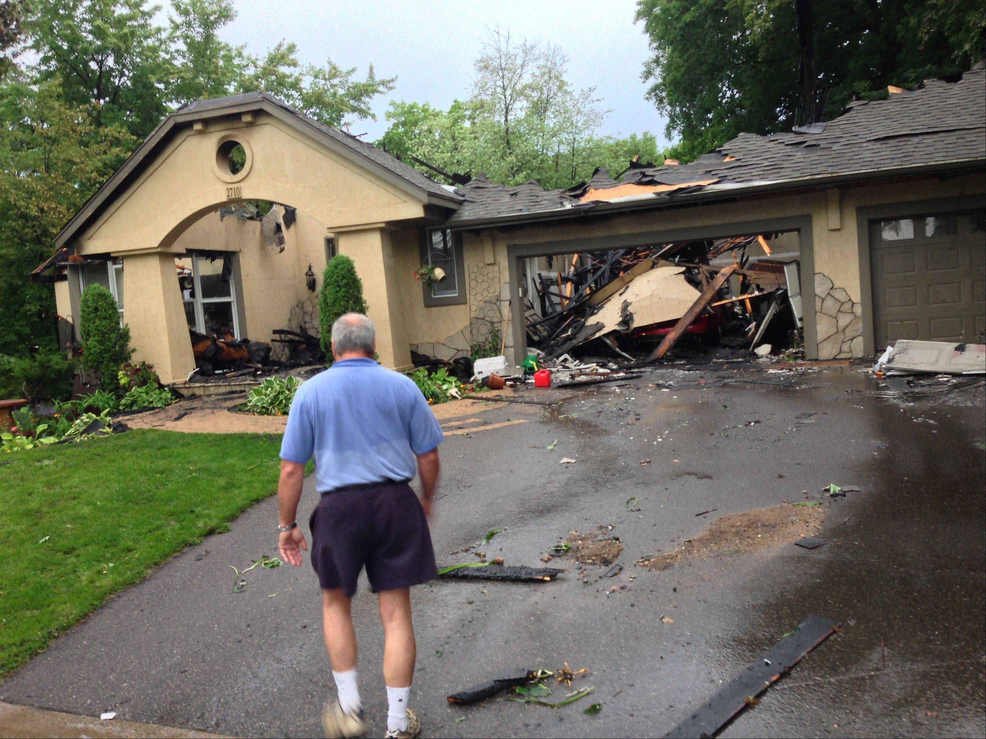A resident looks over a house Friday that was damaged during a storm in Minnetonka, Minn. More severe weather was forecast for Minnesota for later Friday night and early Saturday.