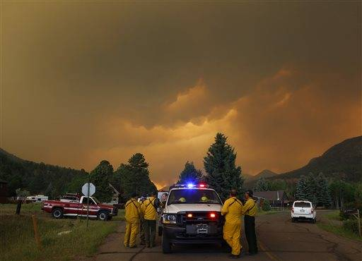 Firefighters stage in a residential area in South Fork, Colo., as they monitor a wildfire that burns west of town on Friday evening June 21, 2013. The town was evacuated and U.S. 160 that passes through it was closed.