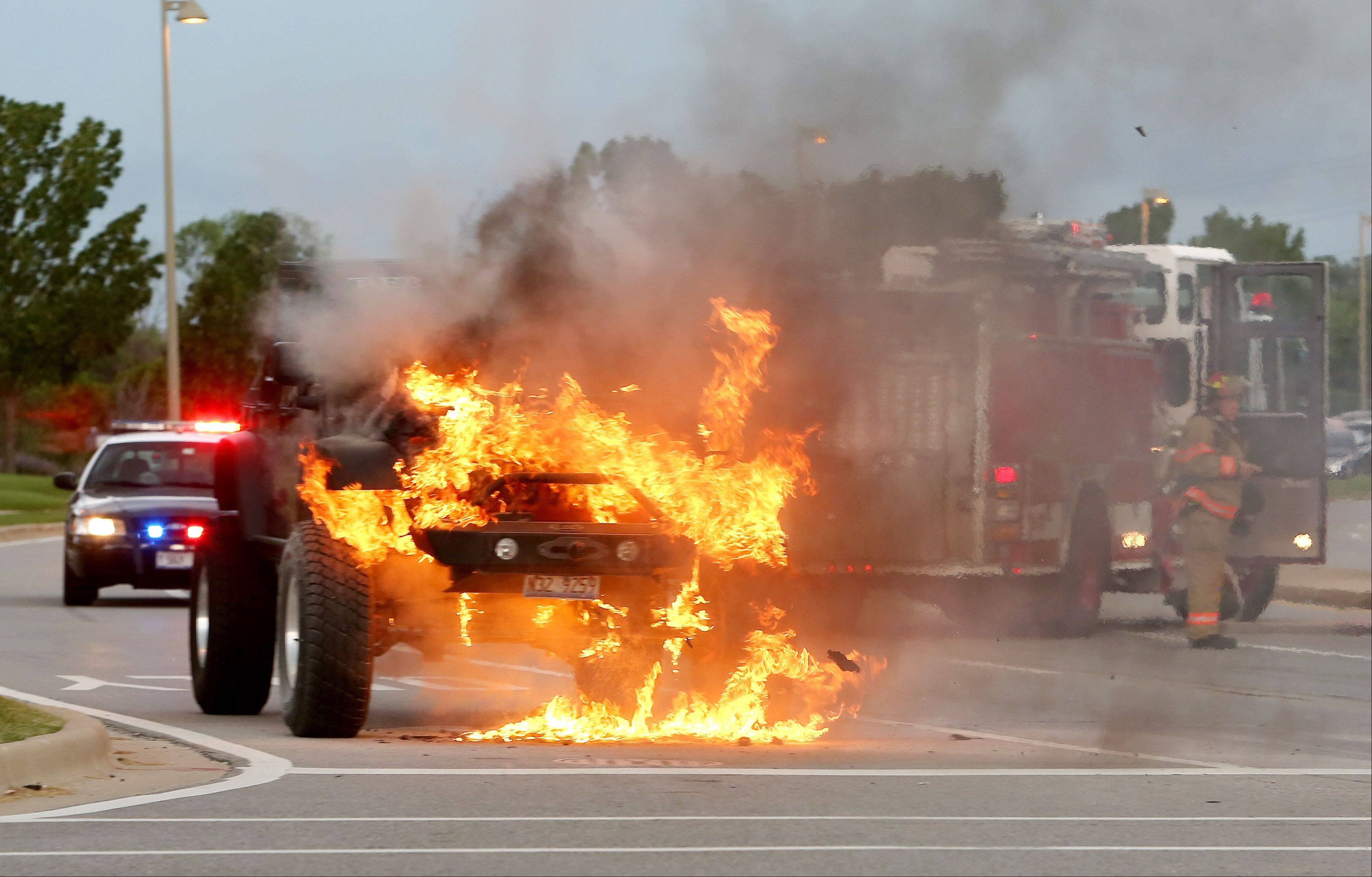 Firefighters arrive after a Jeep caught fire around noon Friday on eastbound Diehl Road at Davis Parkway in Warrenville.