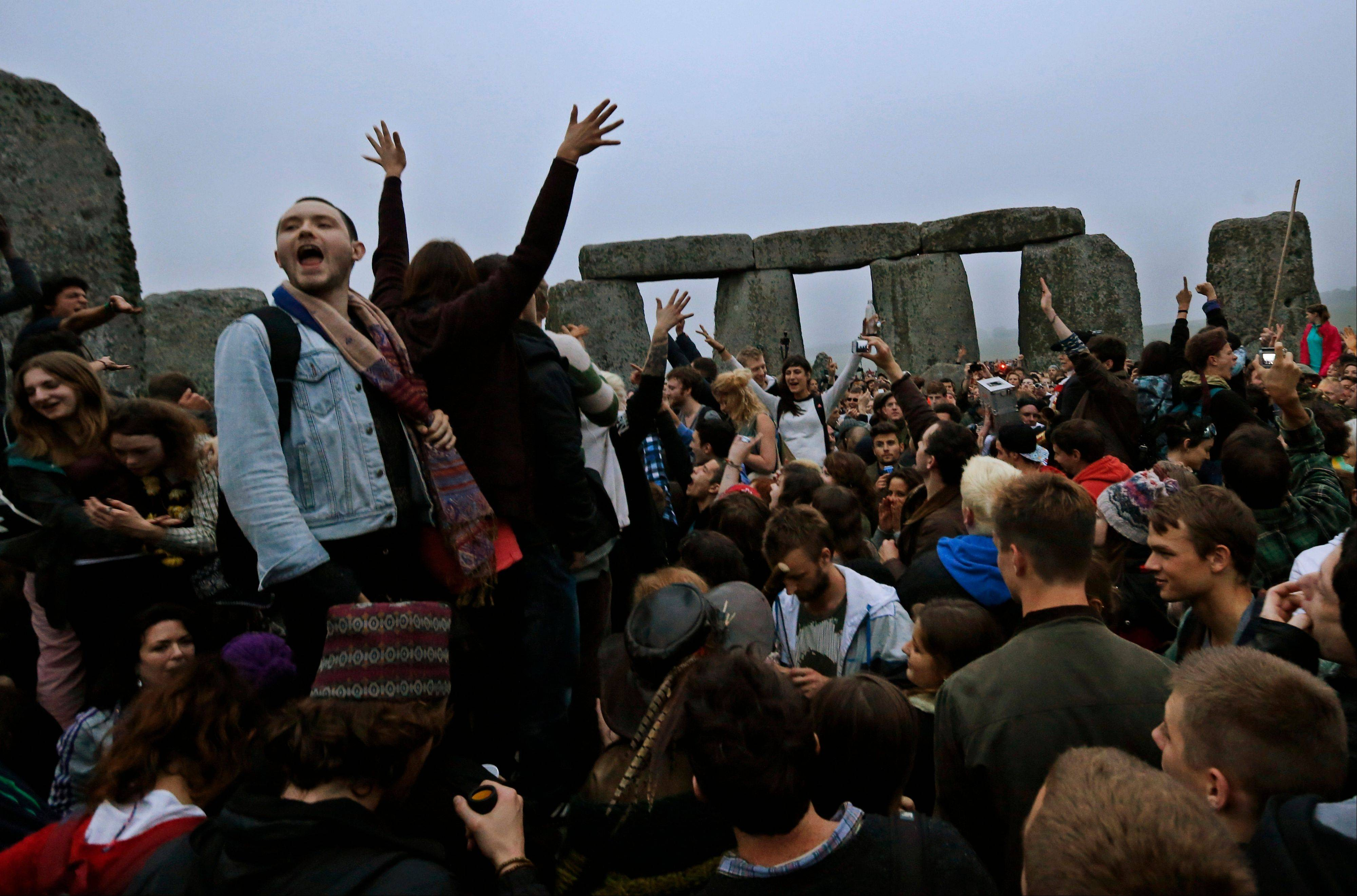 People raise their hands in celebration during the summer solstice shortly after 4:52 a.m. at the prehistoric Stonehenge monument, near Salisbury, England, Friday, June 21, 2013. Following an annual all-night party, thousands of New Agers and neo-pagans danced and whooped in delight at the ancient stone circle Stonehenge, marking the summer solstice, the longest day of the year.