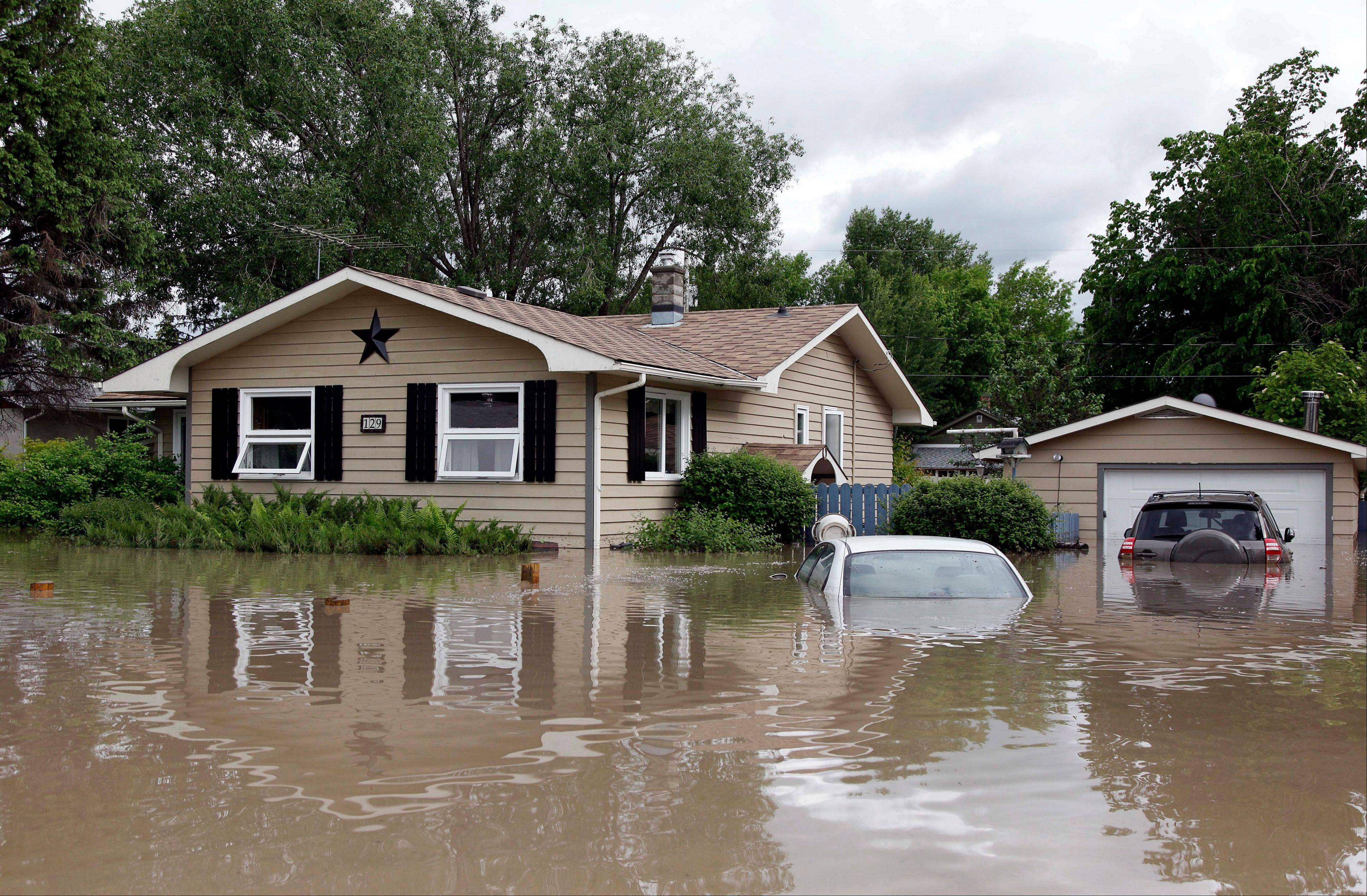 Cars and homes are submerged in floodwaters in High River, Alberta, Thursday, June 20, 2013. Calgary city officials say as many as 100,000 people could be forced from their homes due to heavy flooding in western Canada, while mudslides have forced the closure of the Trans-Canada Highway around the mountain resort towns of Banff and Canmore.