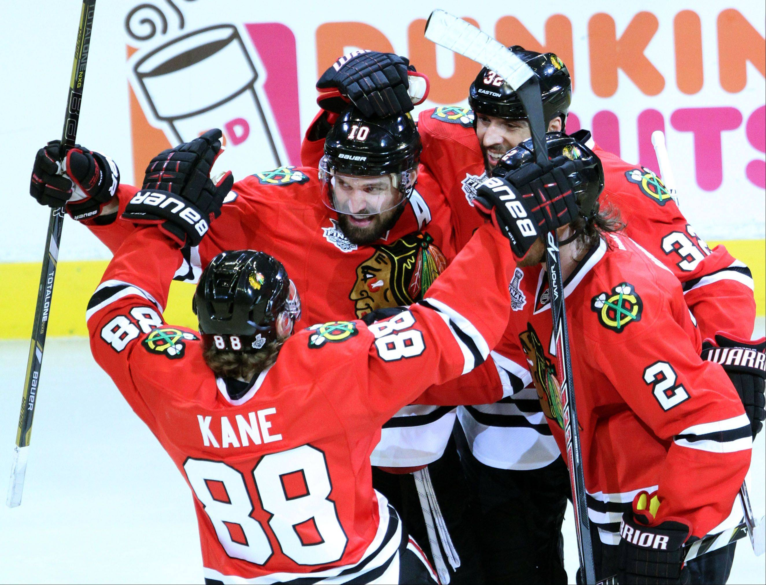 Patrick Sharp, here getting a hug from Patrick Kane and his teammates after scoring in Game 2 of the Stanley Cup Finals, has 10 playoff goals to lead the Hawks into Game 5 against the Boston Bruins at the United Center on Saturday.