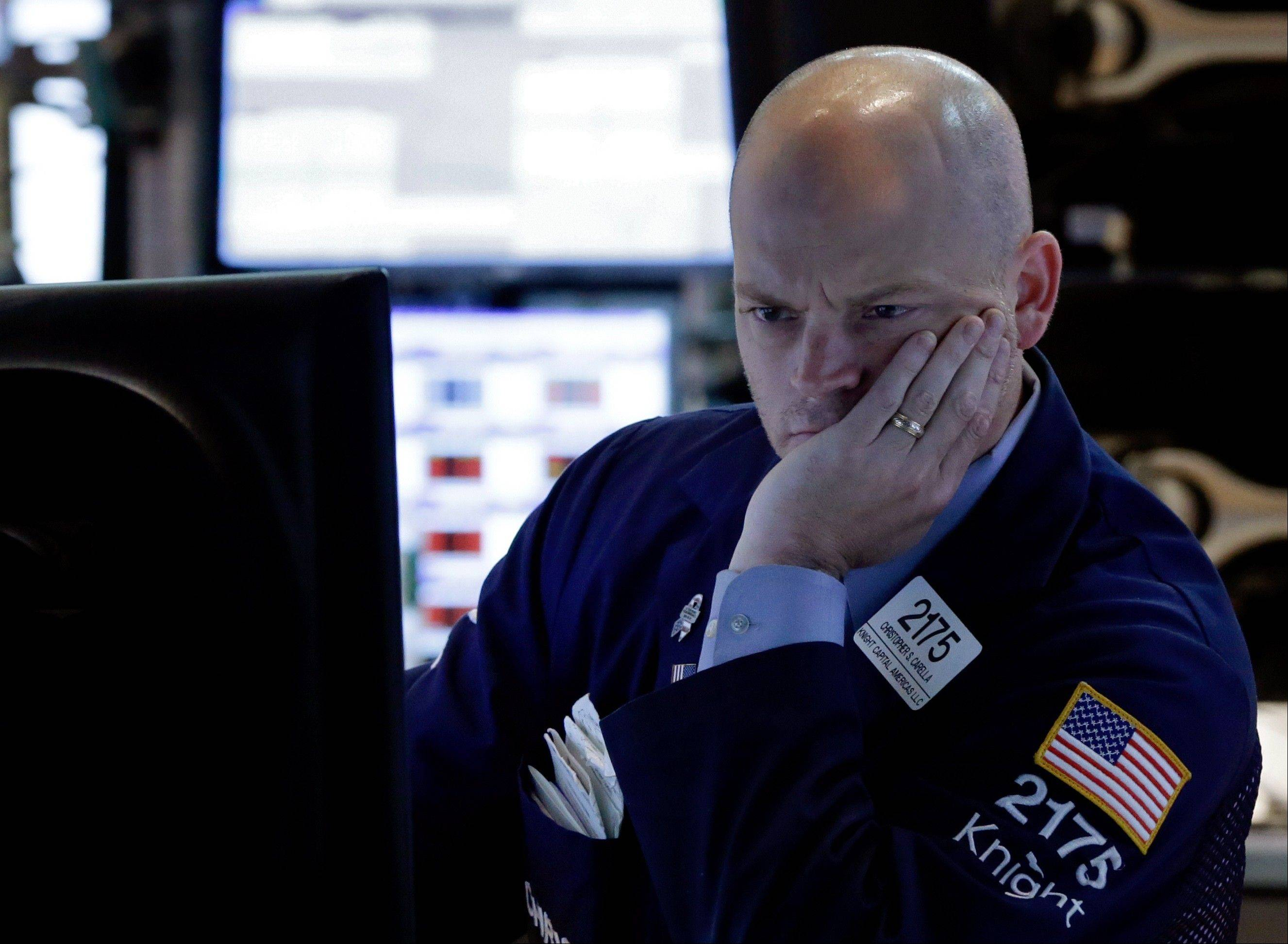 Specialist Christopher Carella watches his screens Thursday as he works on the floor of the New York Stock Exchange.