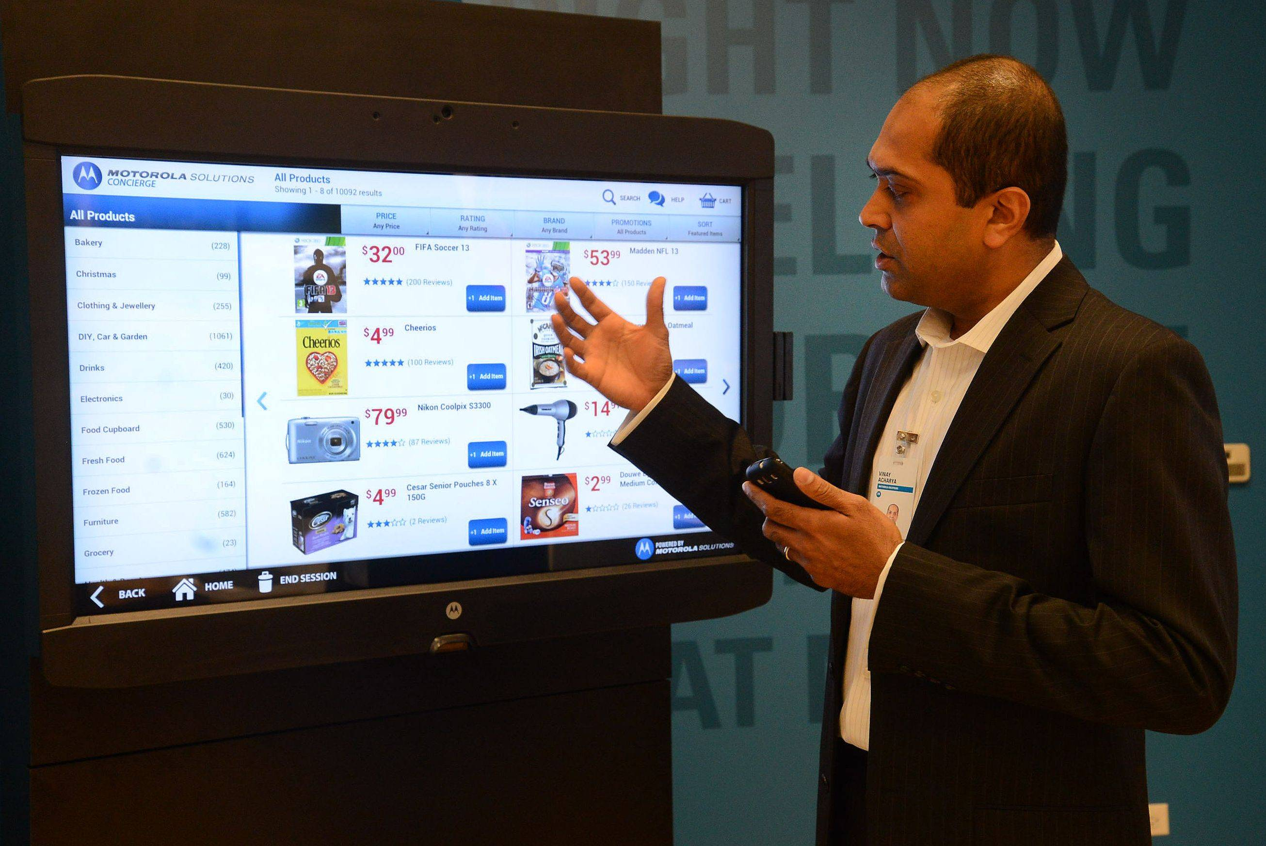 Vinay Acharya demonstrates Customer Concierge, where a customer can shop using a touch screen within a store, during Motorola Solutions Innovation Showcase 2013.