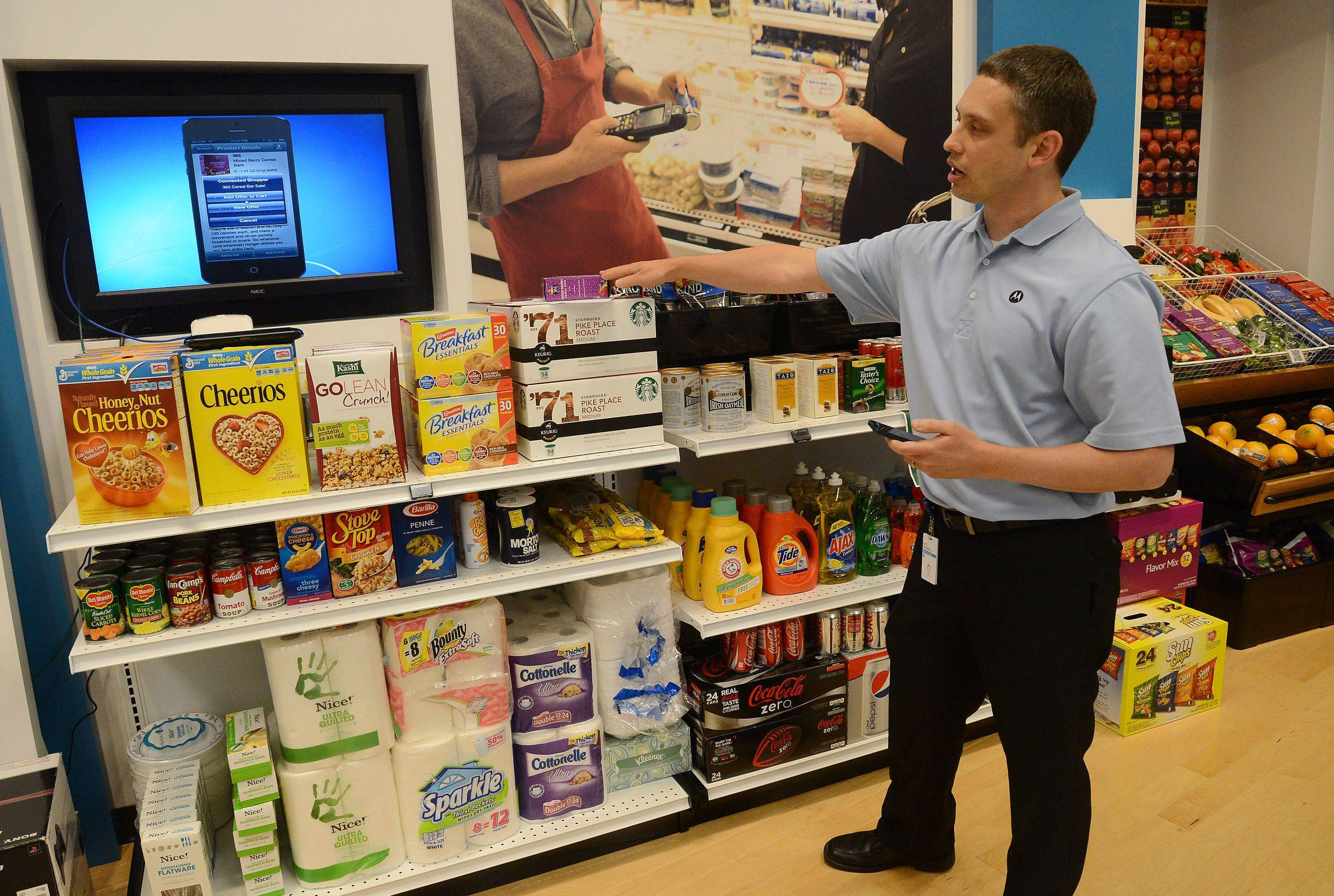 Eric Maxwell demonstrates the Connected Shopper and how a customer scans items with a Smartphone while shopping, during the Motorola Solutions Innovation Showcase 2013.