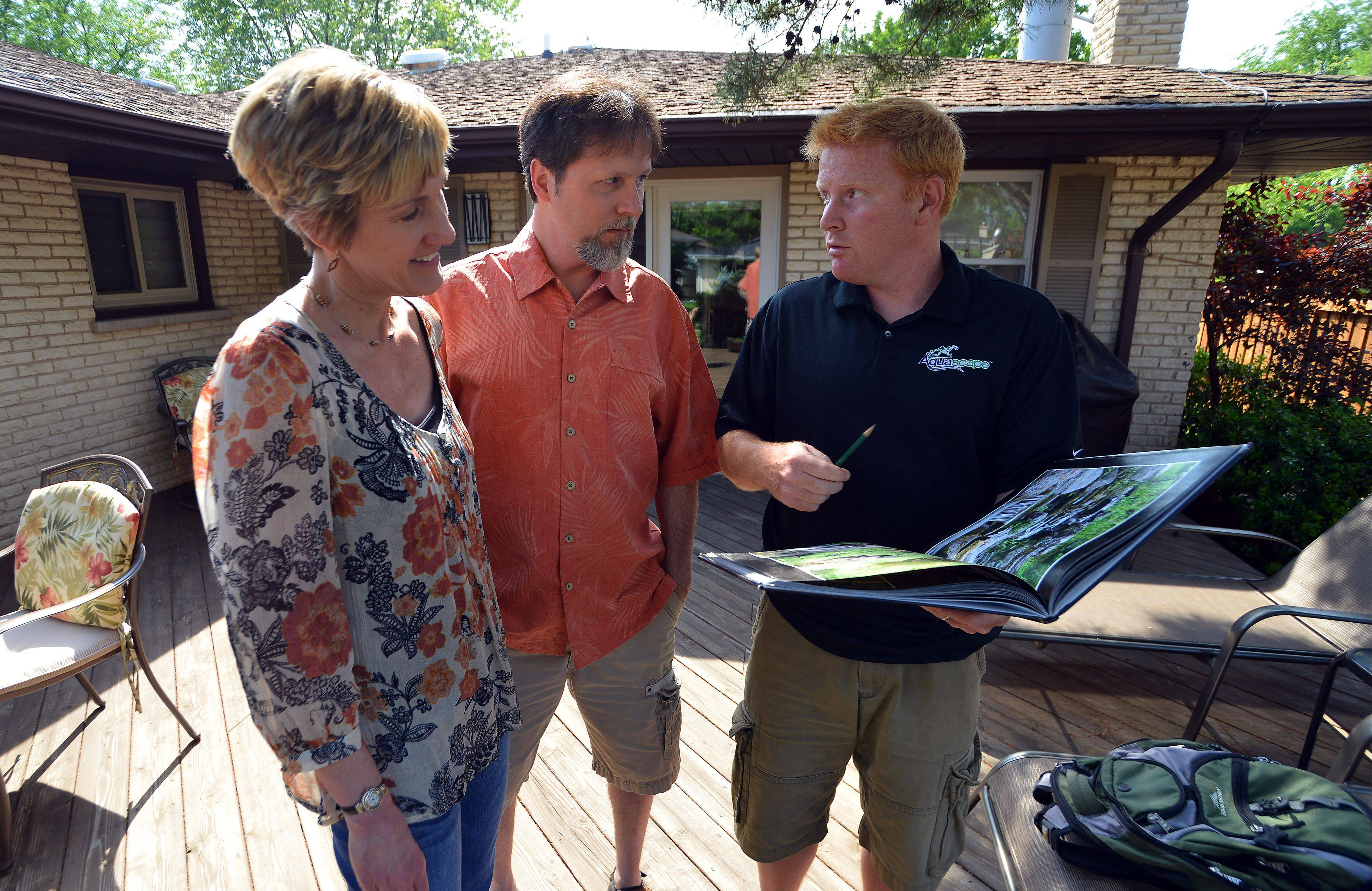 Scott and Amy Bell of Mount Prospect talk with Brian Helfrich, construction manager at Aquascapes of St. Charles, about designing a pond-less waterfall in their backyard, which they won as part of the Daily Herald's Get Your Summer On contest.