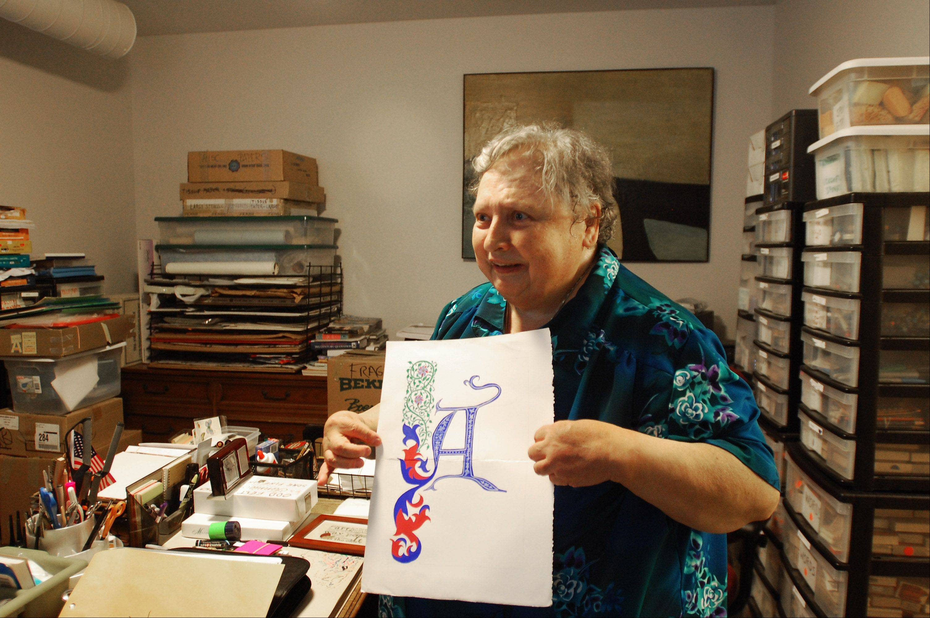 Sister Diane Weifenbach shows off one of her calligraphy pieces in her workspace at Elgin Artspace Lofts in downtown Elgin.