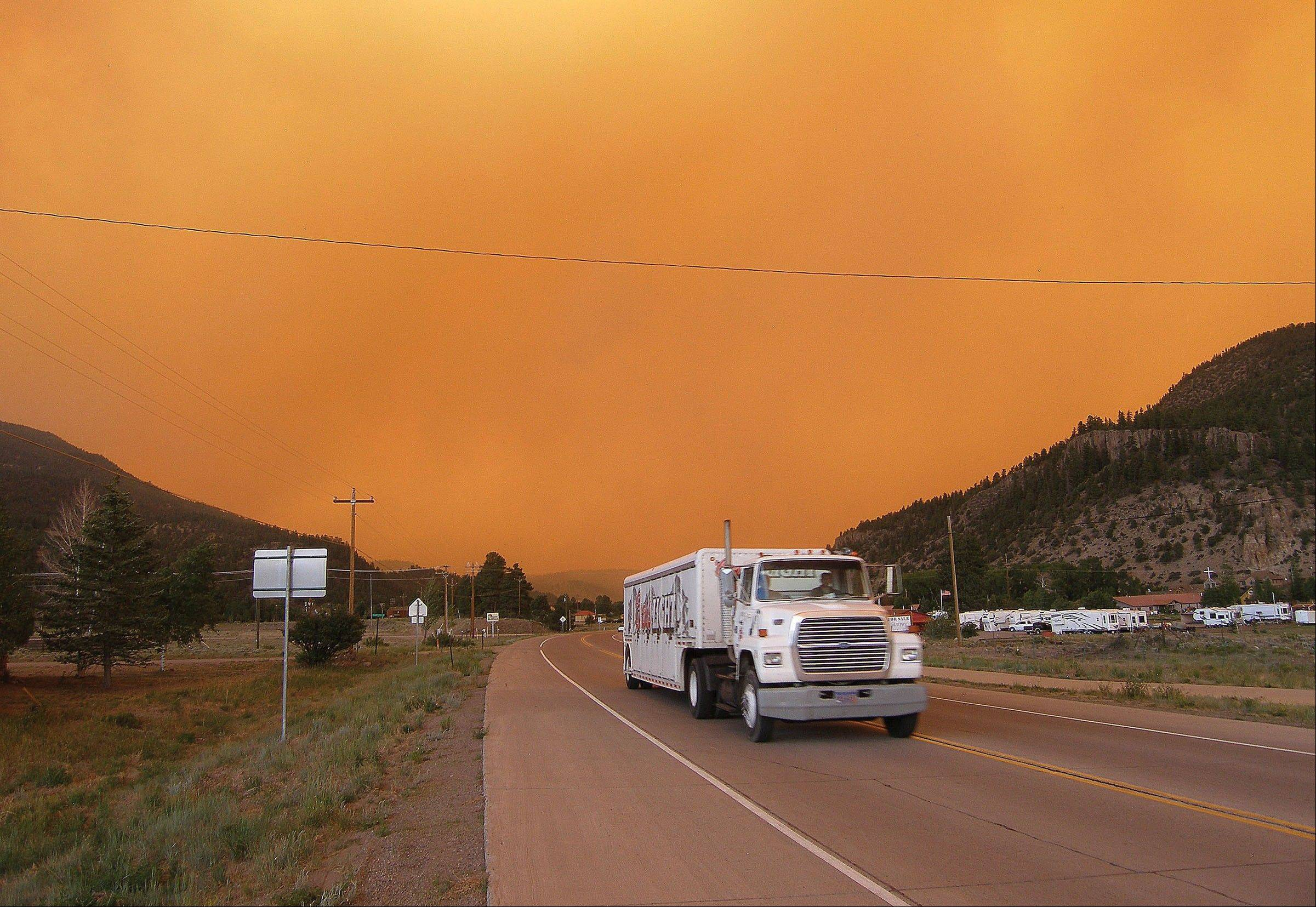Smoke from the West Fork Fire surrounds drivers Friday on Colorado 149 near South Fork. The highway was later closed.