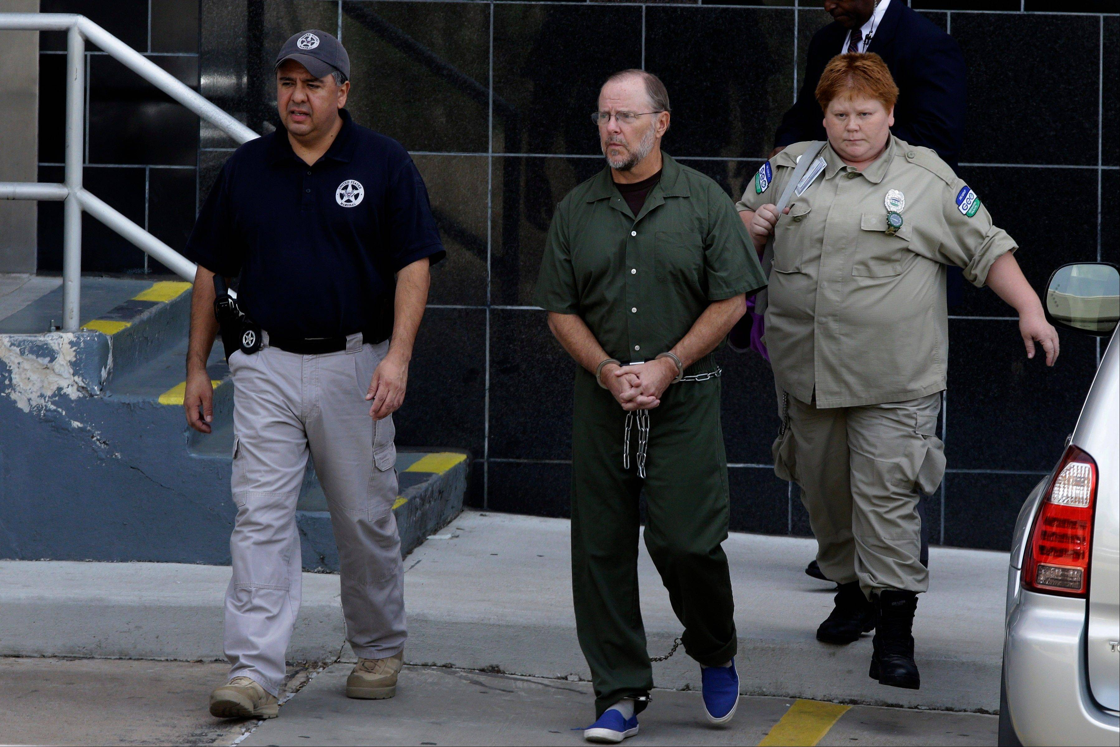 Former Enron CEO Jeffrey Skilling is escorted Friday from the federal courthouse in Houston after being re-sentenced for his role in the energy giant's collapse.