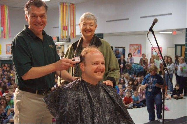 Westgate School music teacher Jerry Berger gets his head shaved for charity during an all-school assembly June 3 by principal Caz Badynee and Arlington Heights District 25 superintendent Sarah Jerome.