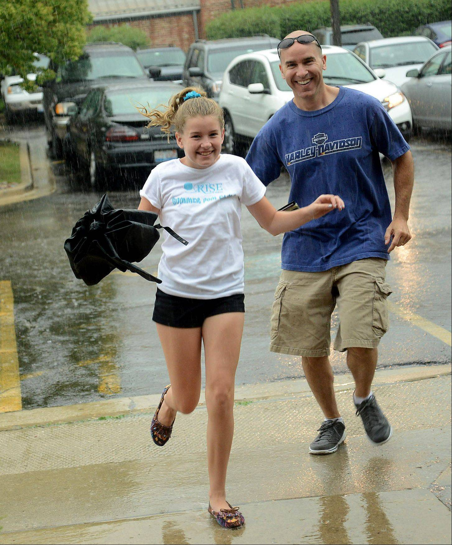 Chris and Madison Melbourn of Schaumburg take cover from Friday's rain in Schaumburg.