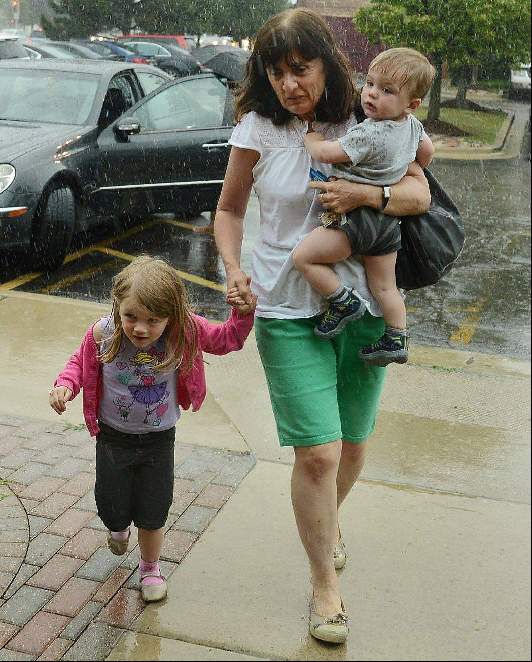 Kay Beyer of Arlington Heights flees the mid-day storm Friday with her grand kids in Schaumburg.