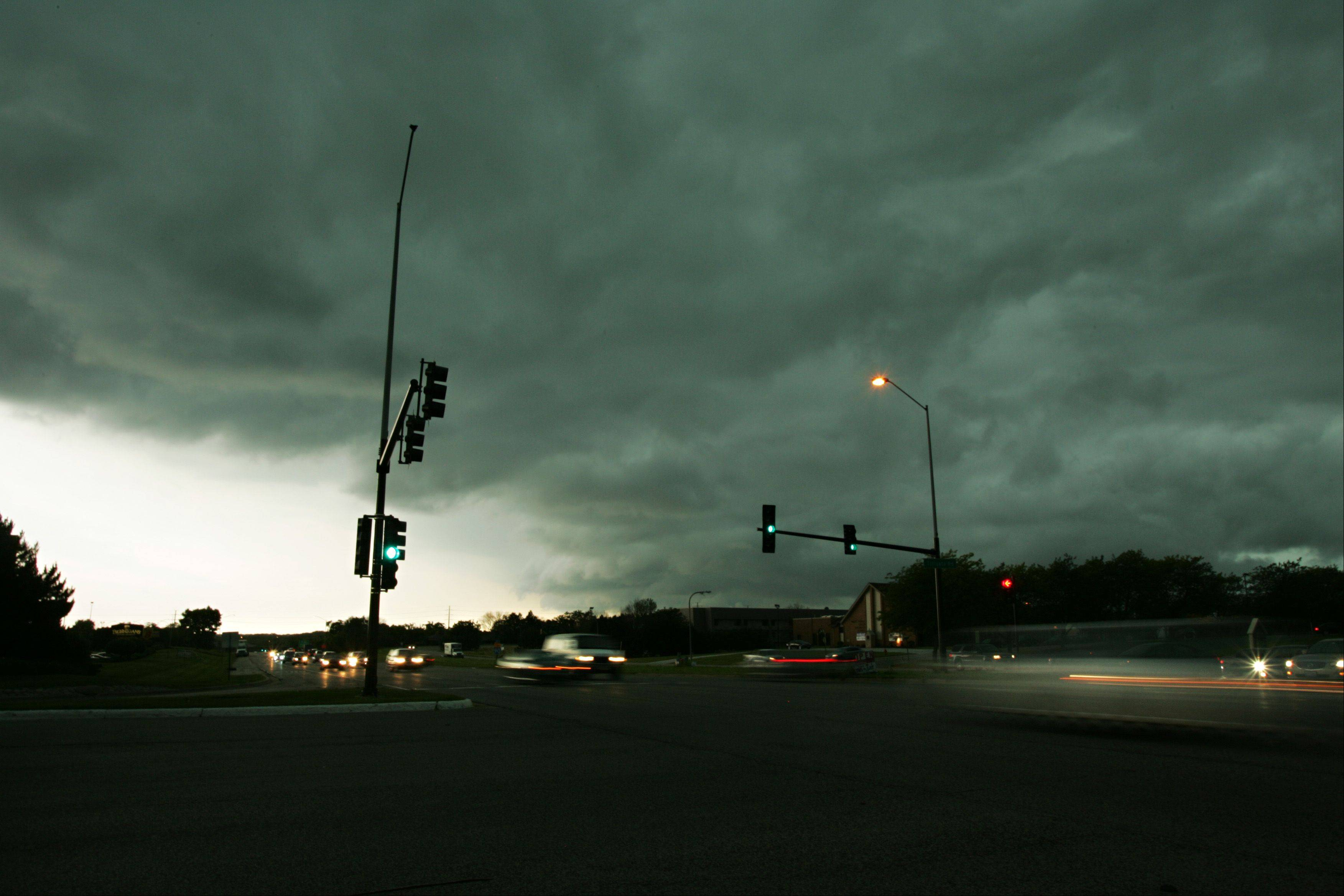 With their headlights on, cars streak past the corner of Route 31 and Tollgate Road Friday as stormy weather rolls through Elgin.