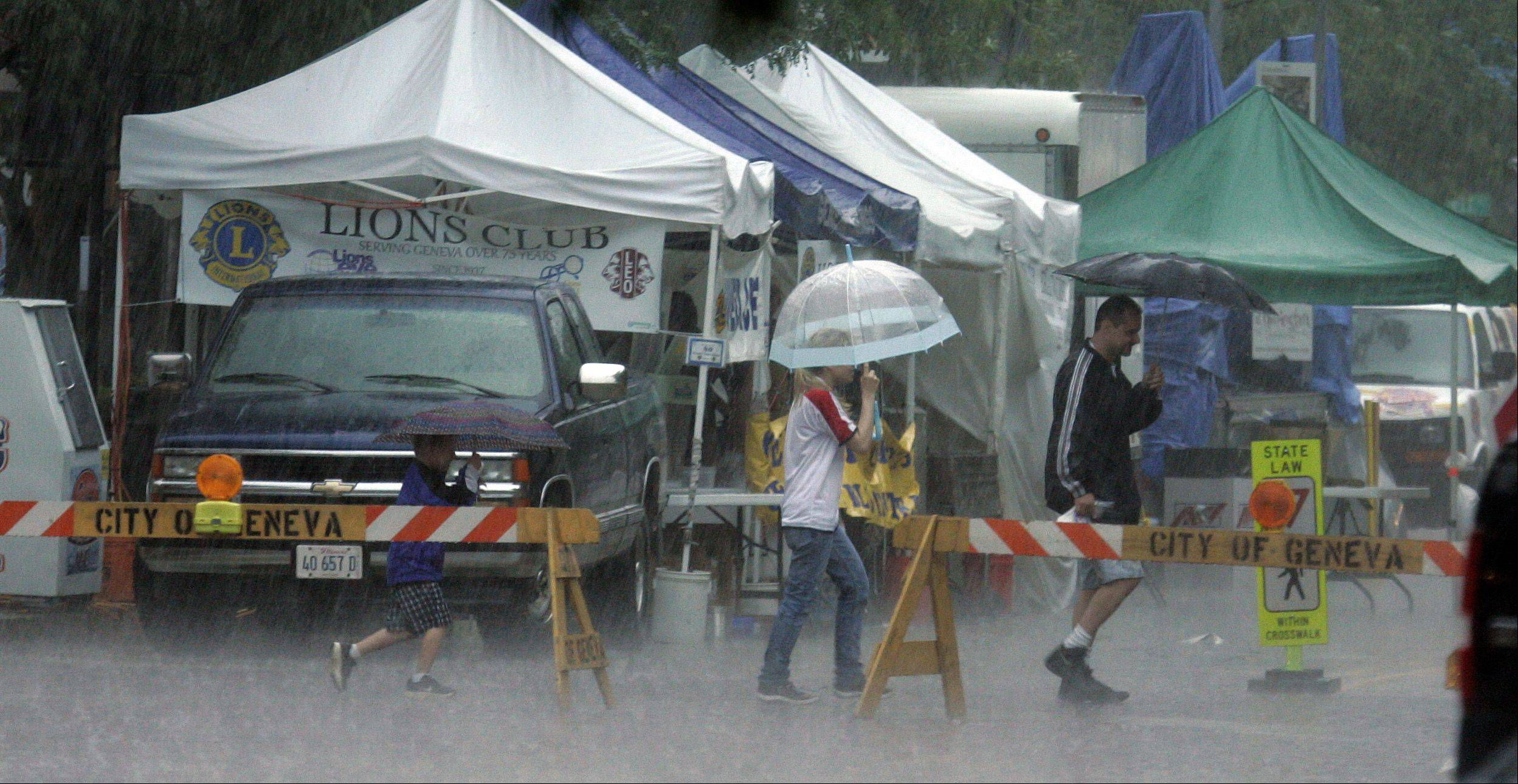 Rain hits as people scurry across Third Street in Geneva Friday. Swedish Days was shut down temporarily because of weather.