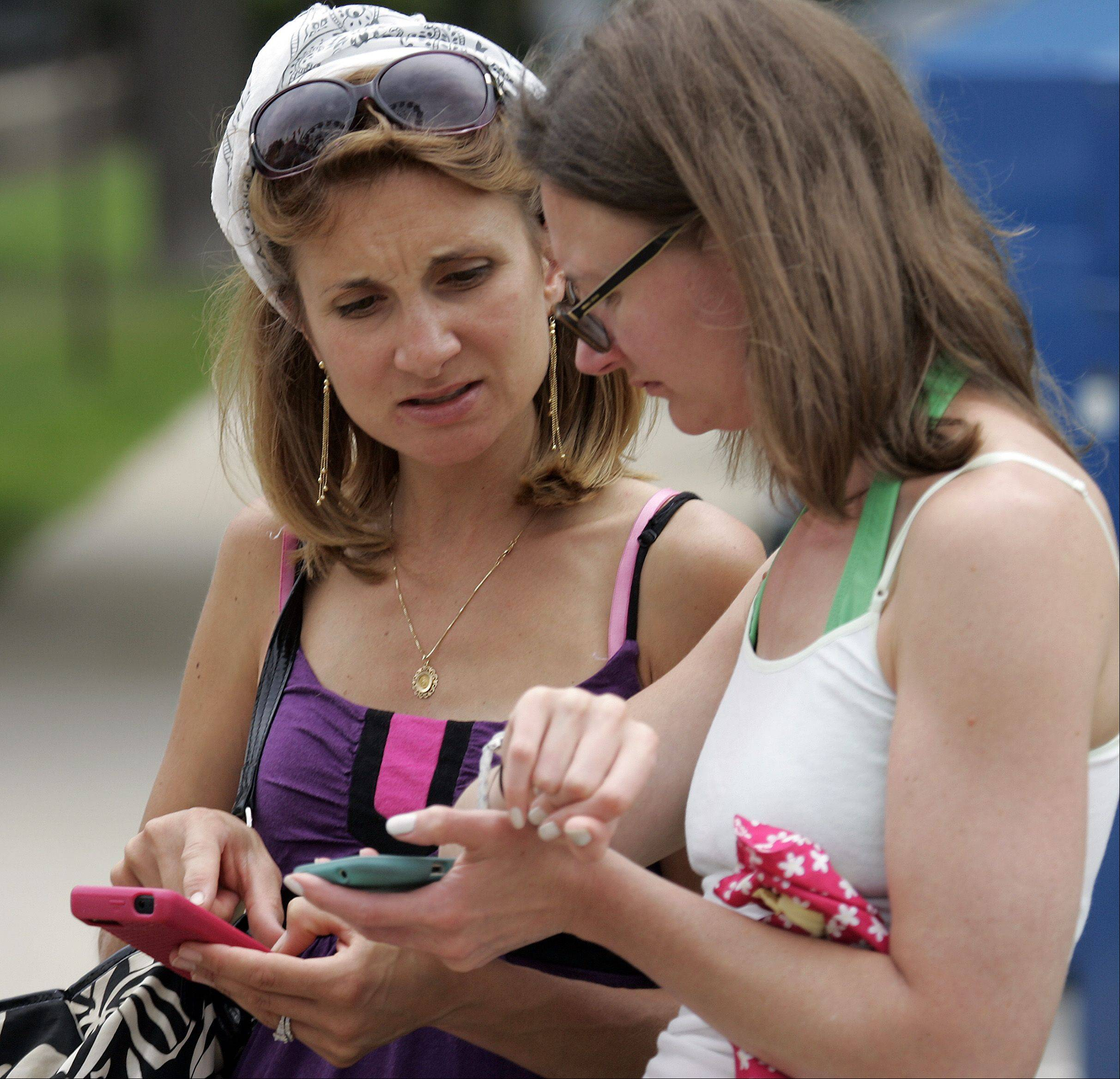 Vanessa Maloney of Geneva and her sister-in-law Sheila Stephenson of Plano, Texas, look at weather reports of Friday afternoon's impending storm on their smartphones at Swedish Days in Geneva.