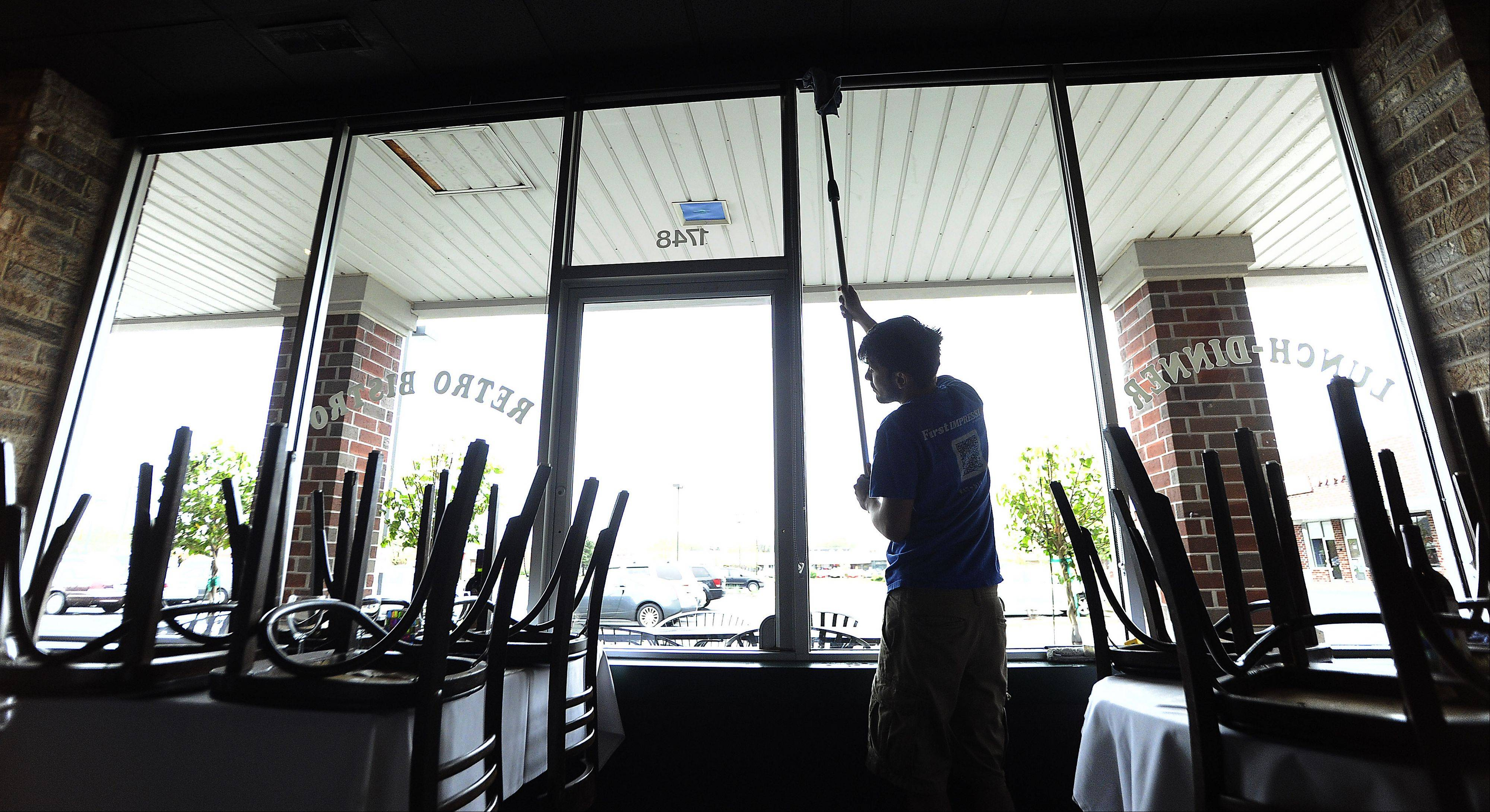 Virgil Pop, 27, of Prospect Heights cleans the inside windows at a Mount Prospect restaurant. He uses a towel at the end of a pole to wipe off the excess water on the ledge.