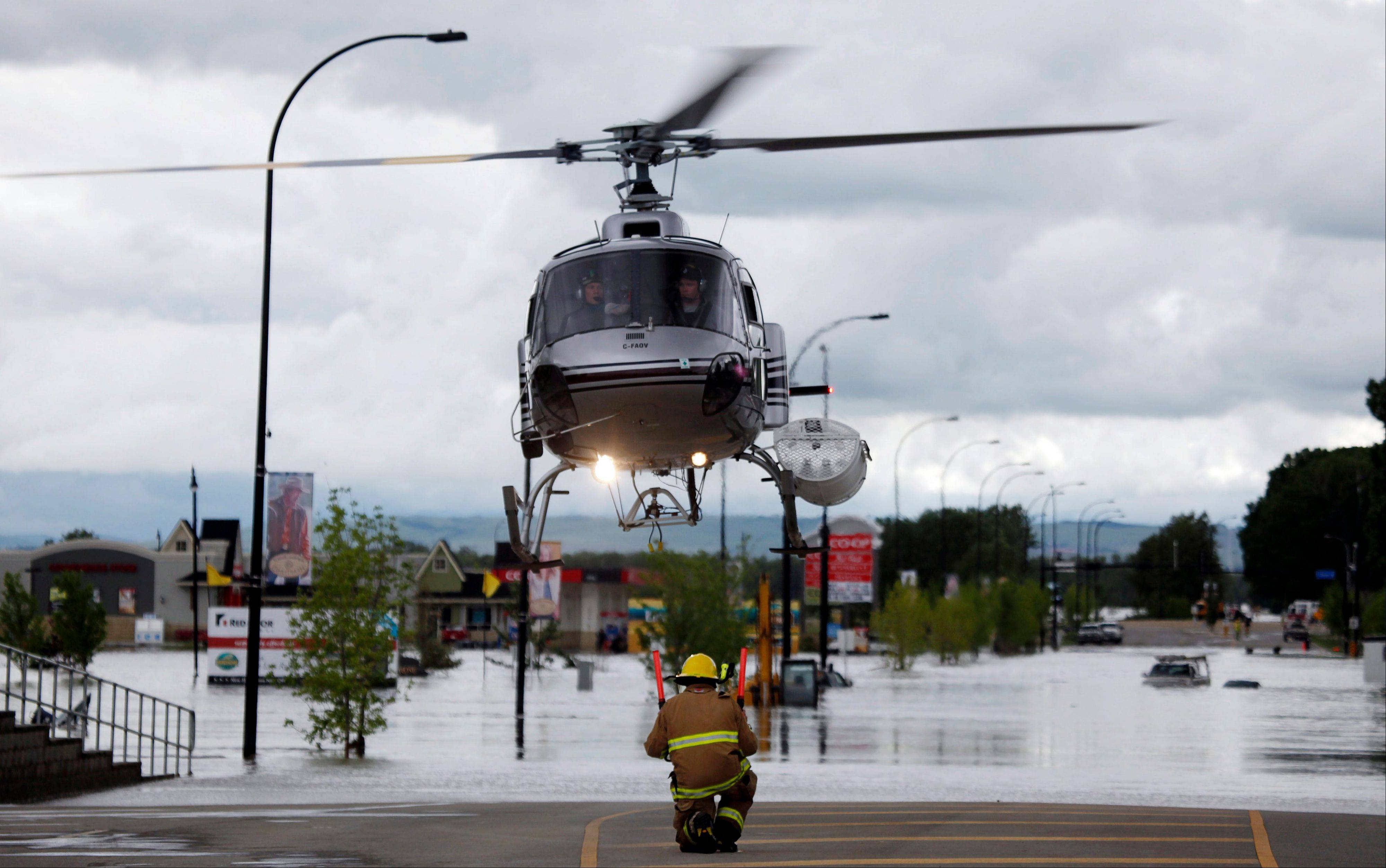 A helicopter carrying evacuated residents lands on a road in High River, Alta., Thursday, June 20, 2013. Calgary city officials say as many as 100,000 people could be forced from their homes due to heavy flooding in western Canada.