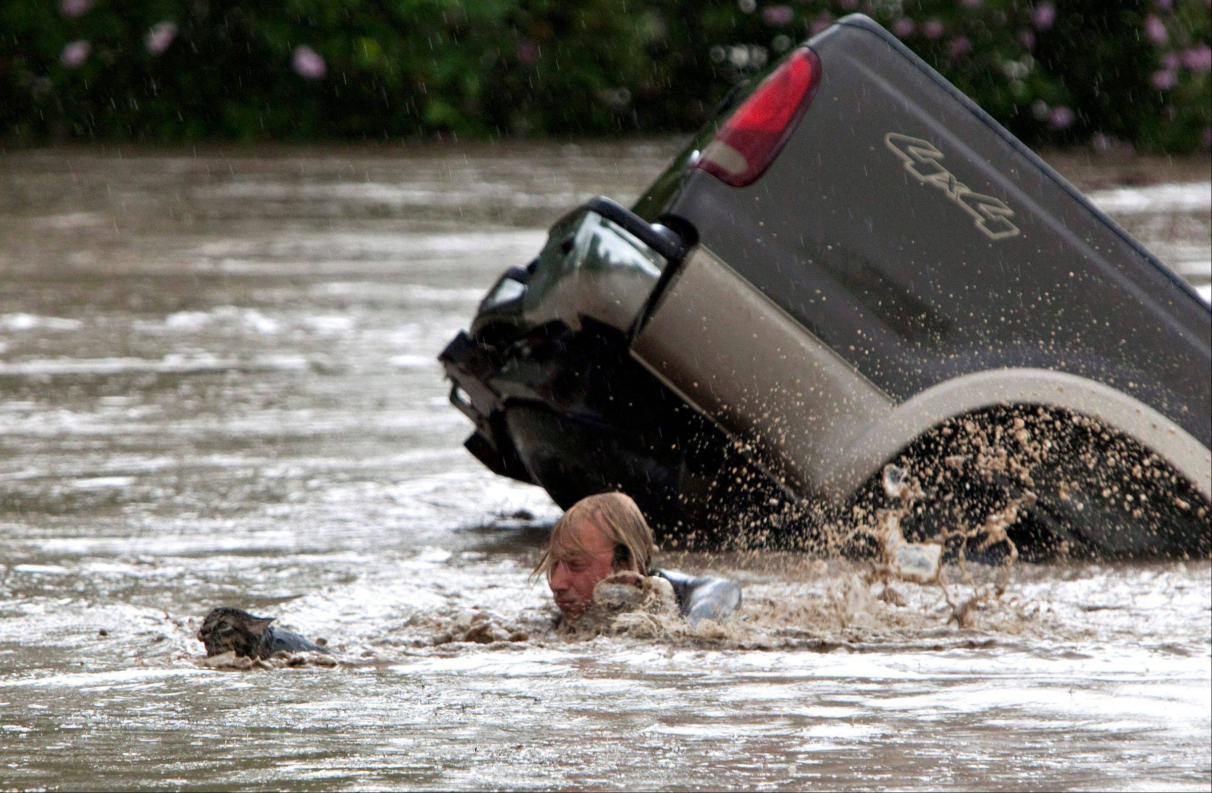 Kevan Yaets swims after his cat Momo to safety as the floodwaters sweep him downstream after submerging his truck in High River, Alberta on Thursday, June 20, 2013 after the Highwood River overflowed its banks. Hundreds of people have been evacuated with volunteers and emergency crews helping to aid stranded residents.