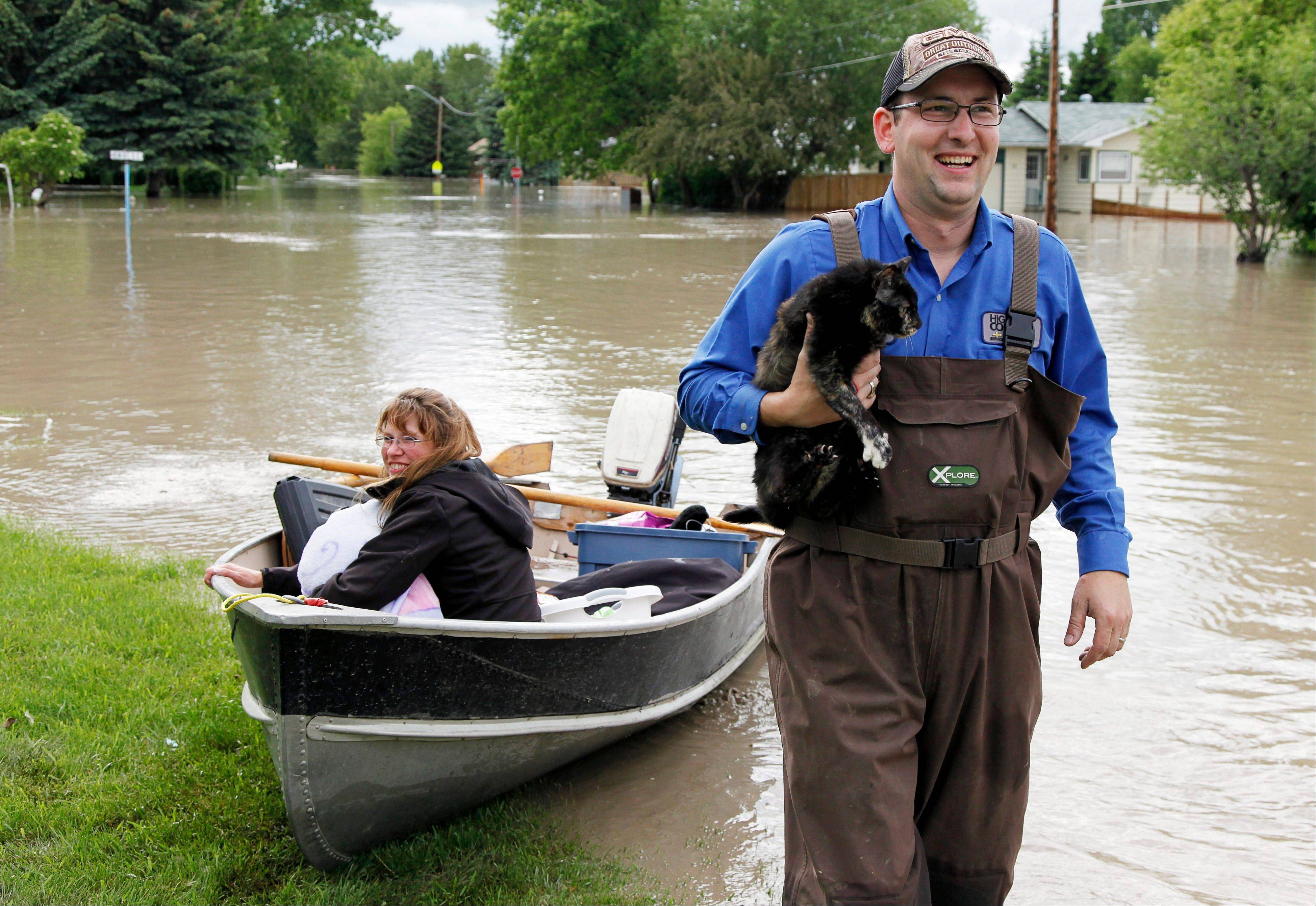 Roger Poirier, holds his family's cat, Smartie, as his wife Crystal looks on after rescuing it from their flooded house in High River, Alta., Thursday, June 20, 2013.