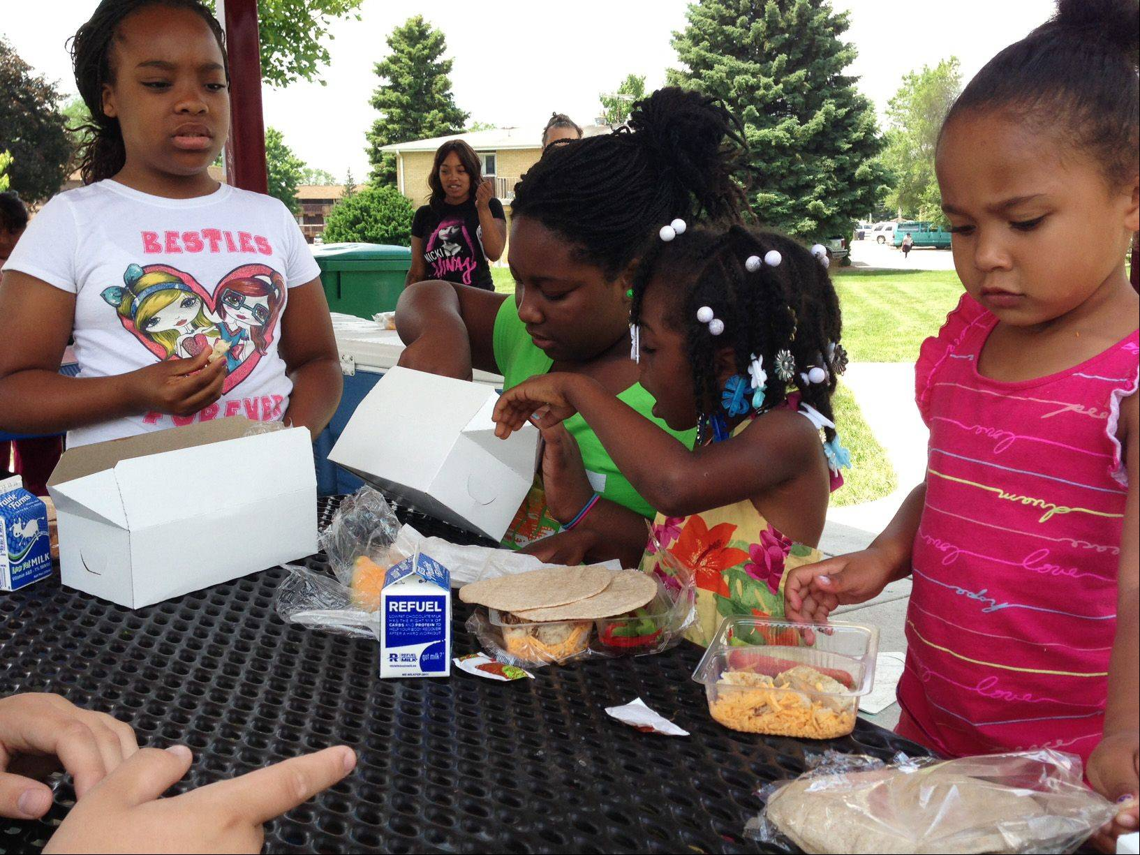 Geniah Phillips, 10, from left, Maya Lymas, 10, Genia Phillips, 5, and Raniya Freeney, 4, took part Wednesday in the free summer lunch program offered at Cornerstone Park in Elgin. The lunches are donated by the Northern Illinois Food Bank.