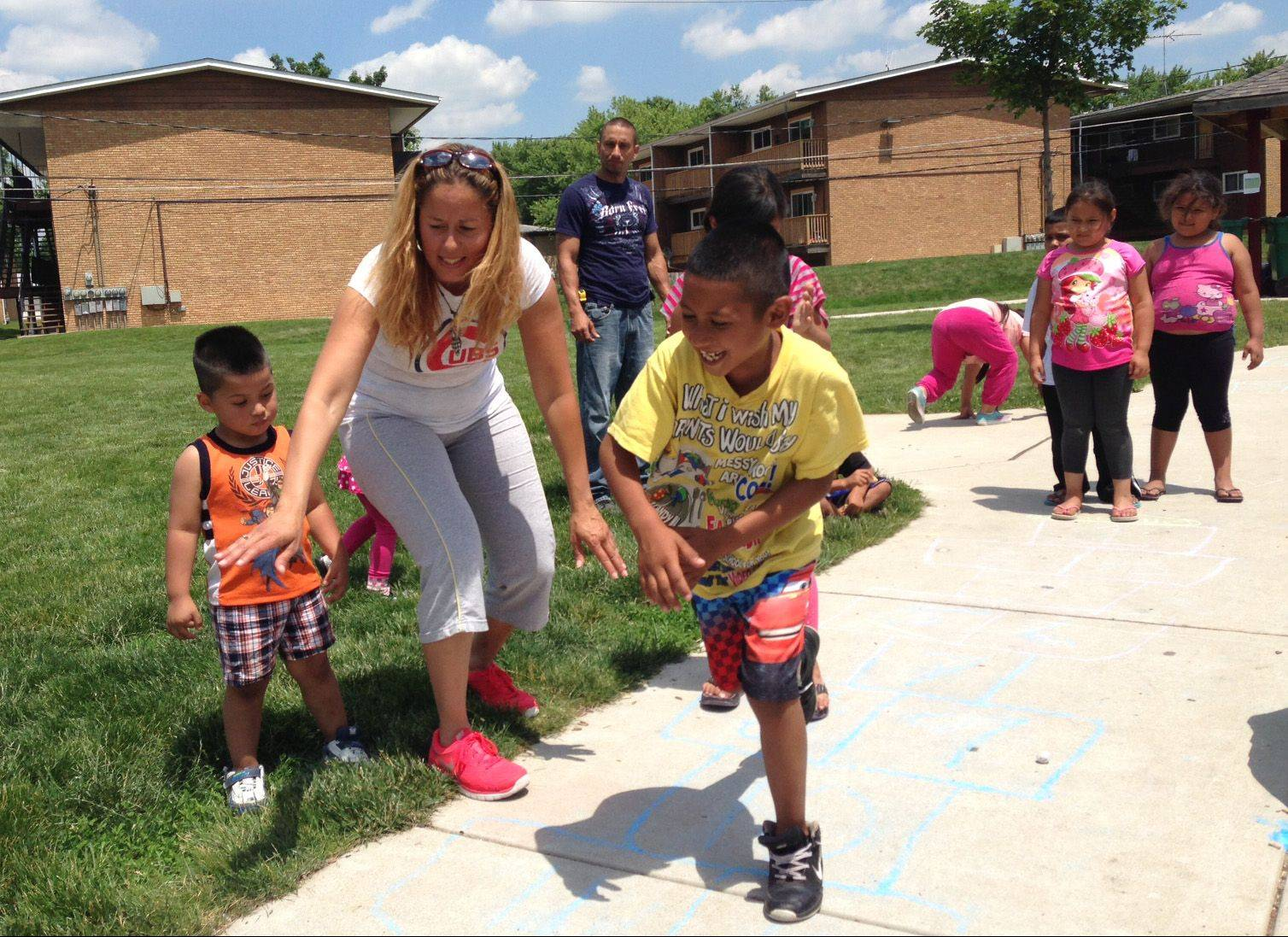 "Hugo Rea, 8, plays a game of hopscotch while volunteer Nordita Crespo cheers him on at Cornerstone Park in Elgin during the ""drop-in playground"" activities that are part of the free summer lunch program offered to Elgin-area children younger than 18."