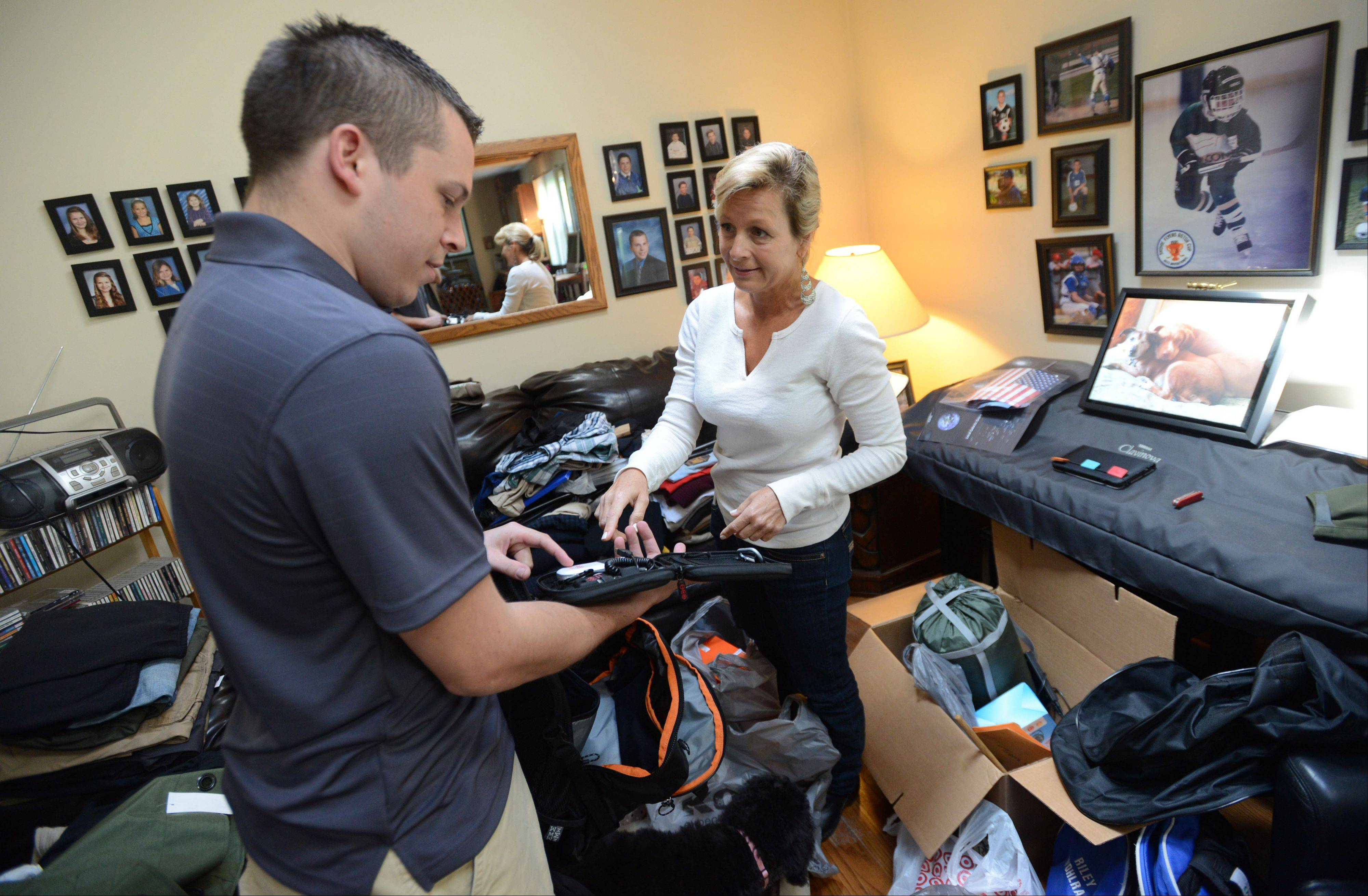 Travis Wohlrab shows his mom, Linda, a solar charging device for his cellphone as he packs for his trip to Africa for the Peace Corps.