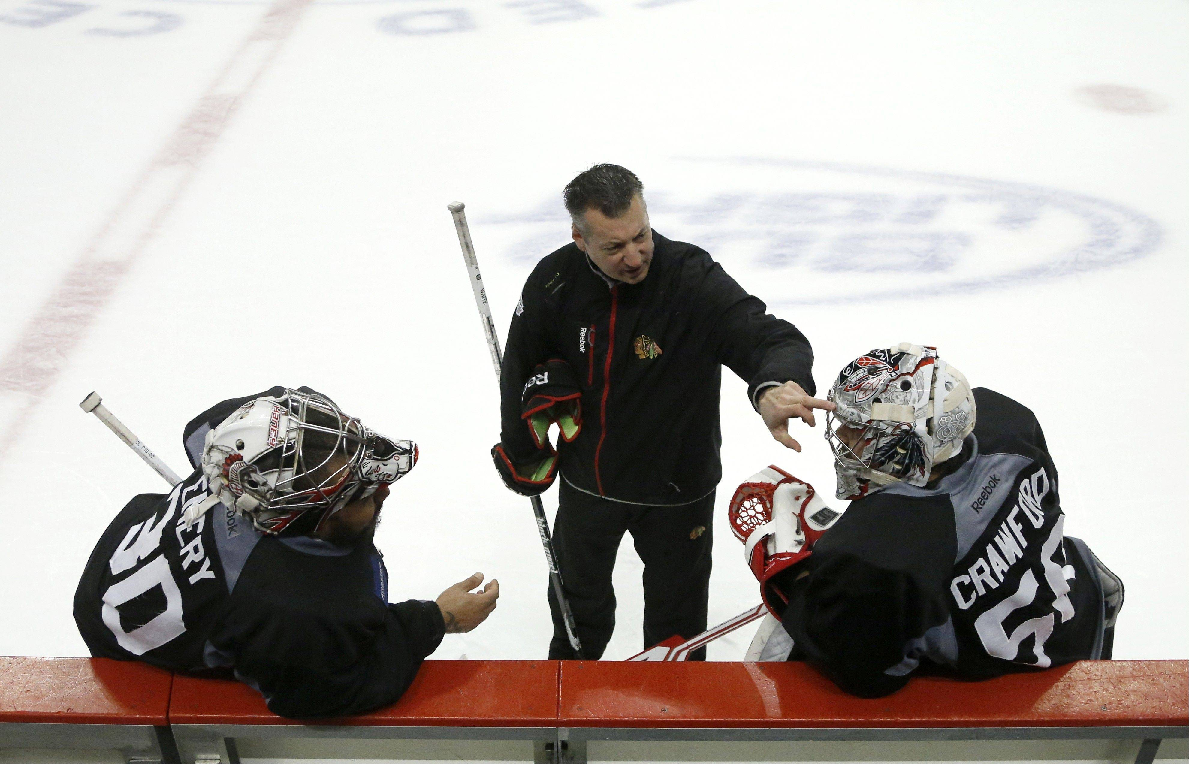Blackhawks goalie coach Stephane Waite, center, talks to goalies Ray Emery, left, and Corey Crawford during practice Friday. Crawford will be in the net for Game 5 on Saturday against Boston.