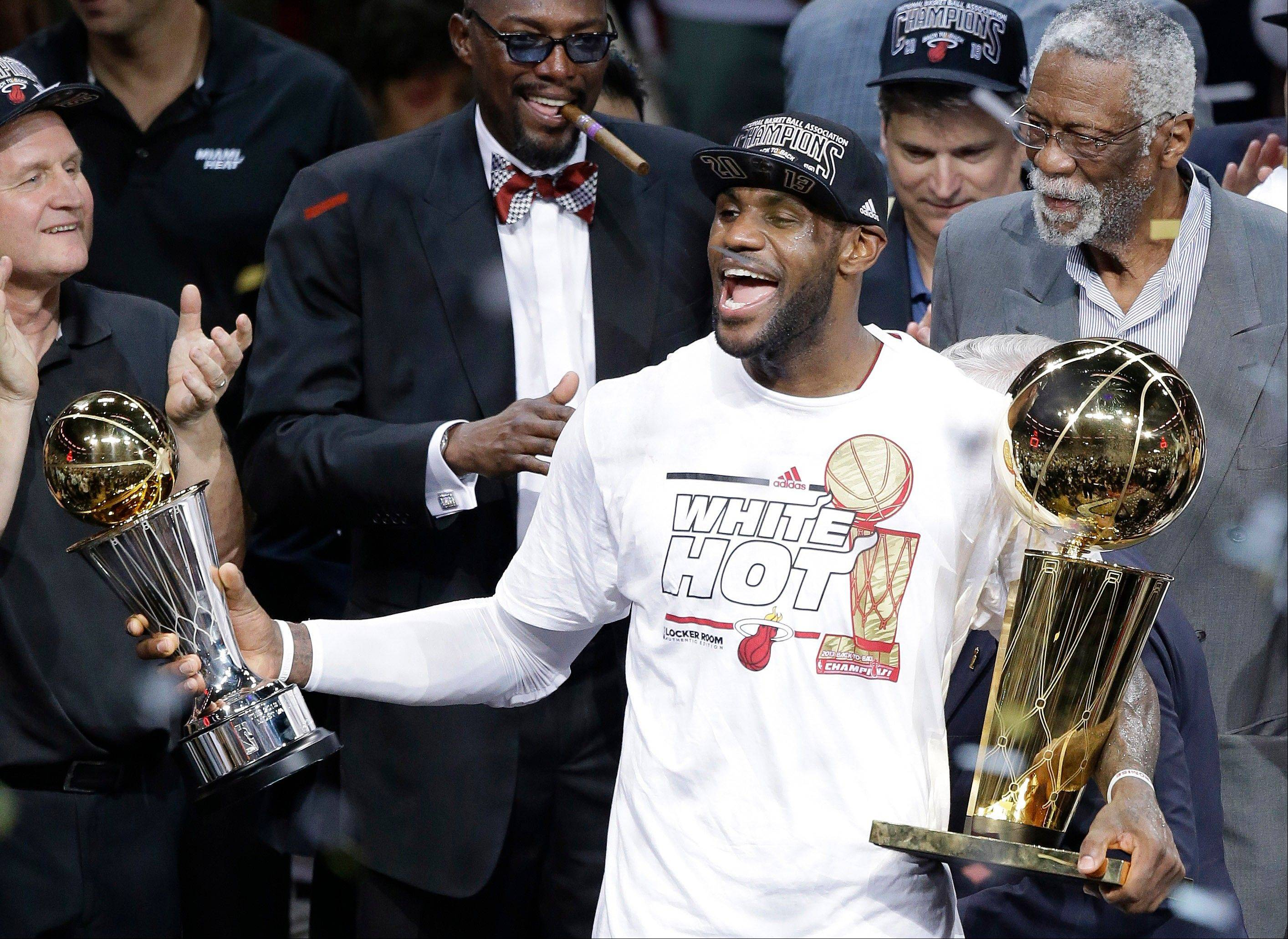 The Miami Heat's LeBron James, left, holding the Larry O'Brien NBA Championship Trophy and his Bill Russell NBA Finals Most Valuable Player Award after Game 7 of the NBA basketball championship game against the San Antonio Spurs, Friday, June 21, 2013, in