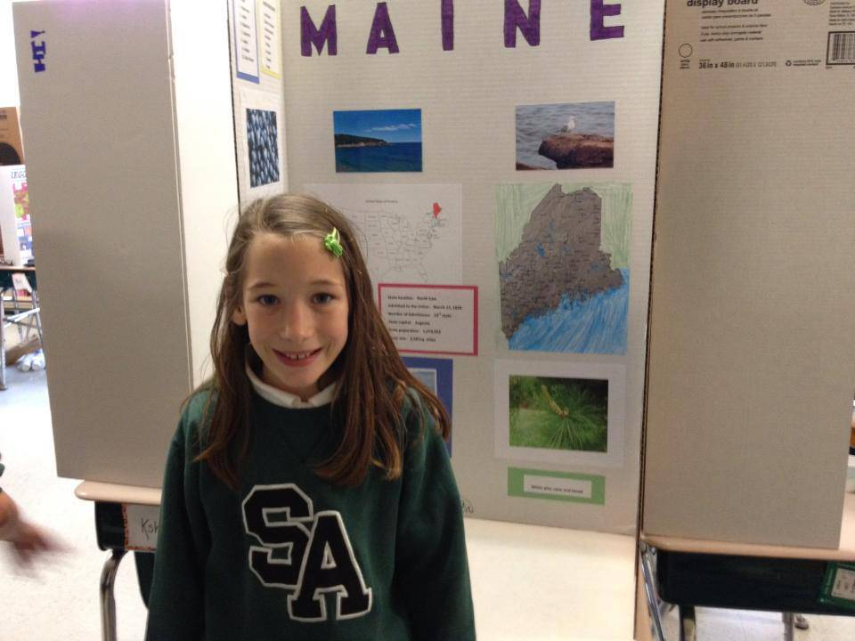 Saint Alphonsus fourth grade student Marianna Maslanka displays her State Project at the school. The State Project is just one of the many pieces of the Saint Alphonsus curriculum that helps students perform well on their Terra Nova tests.
