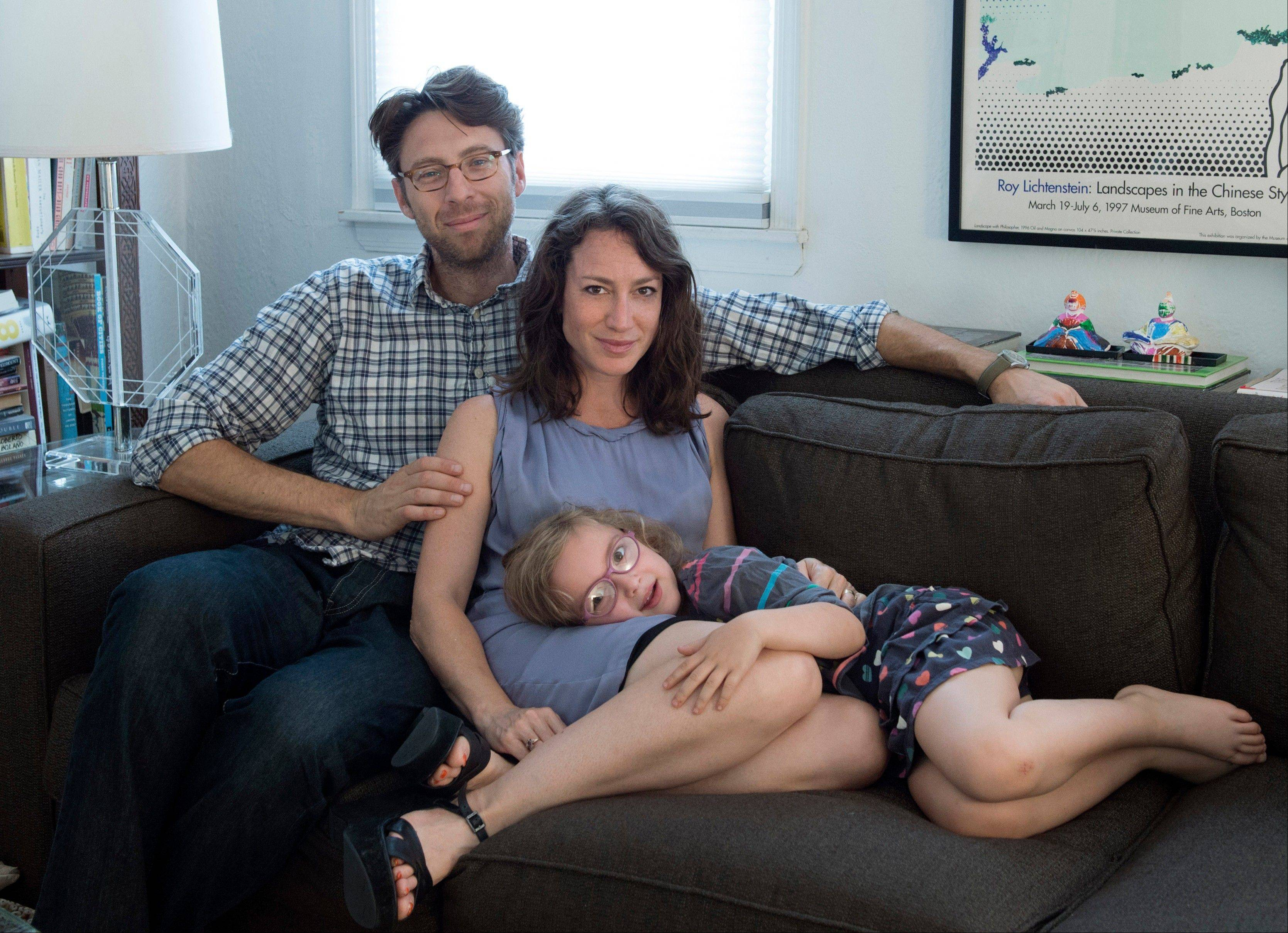 "Justin Lane, left, Lauren Sandler and Dahlia Lane at their home in the Brooklyn borough of New York. Sandler delves into the myths and misconceptions about singletons in a new book, ""One and Only."""