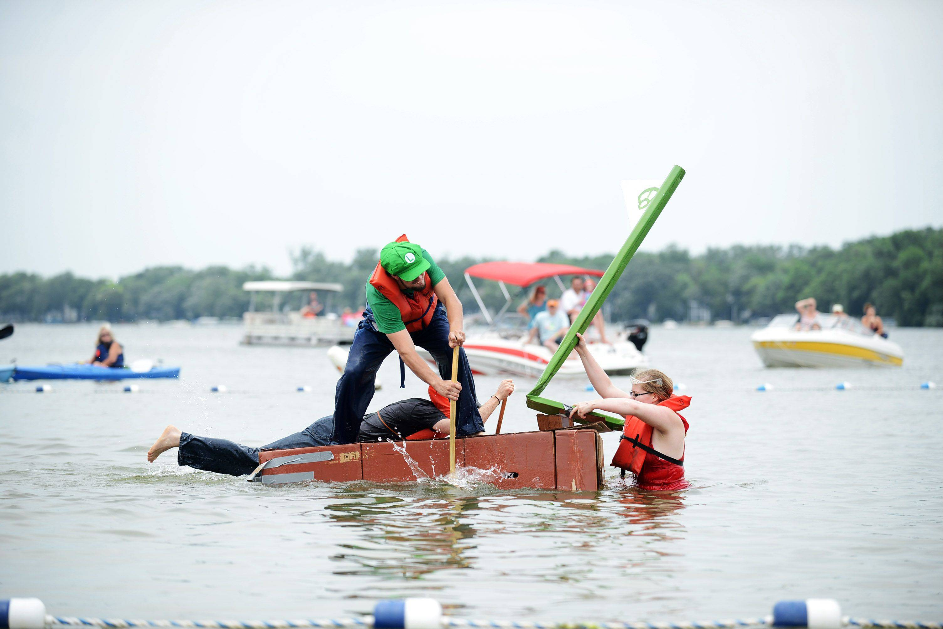 Team Baby Peach struggles to keep the front half of their boat afloat at the 29th annual America�s Cardboard Cup Regatta. The event took place Saturday at Crystal Lake�s Main Beach.