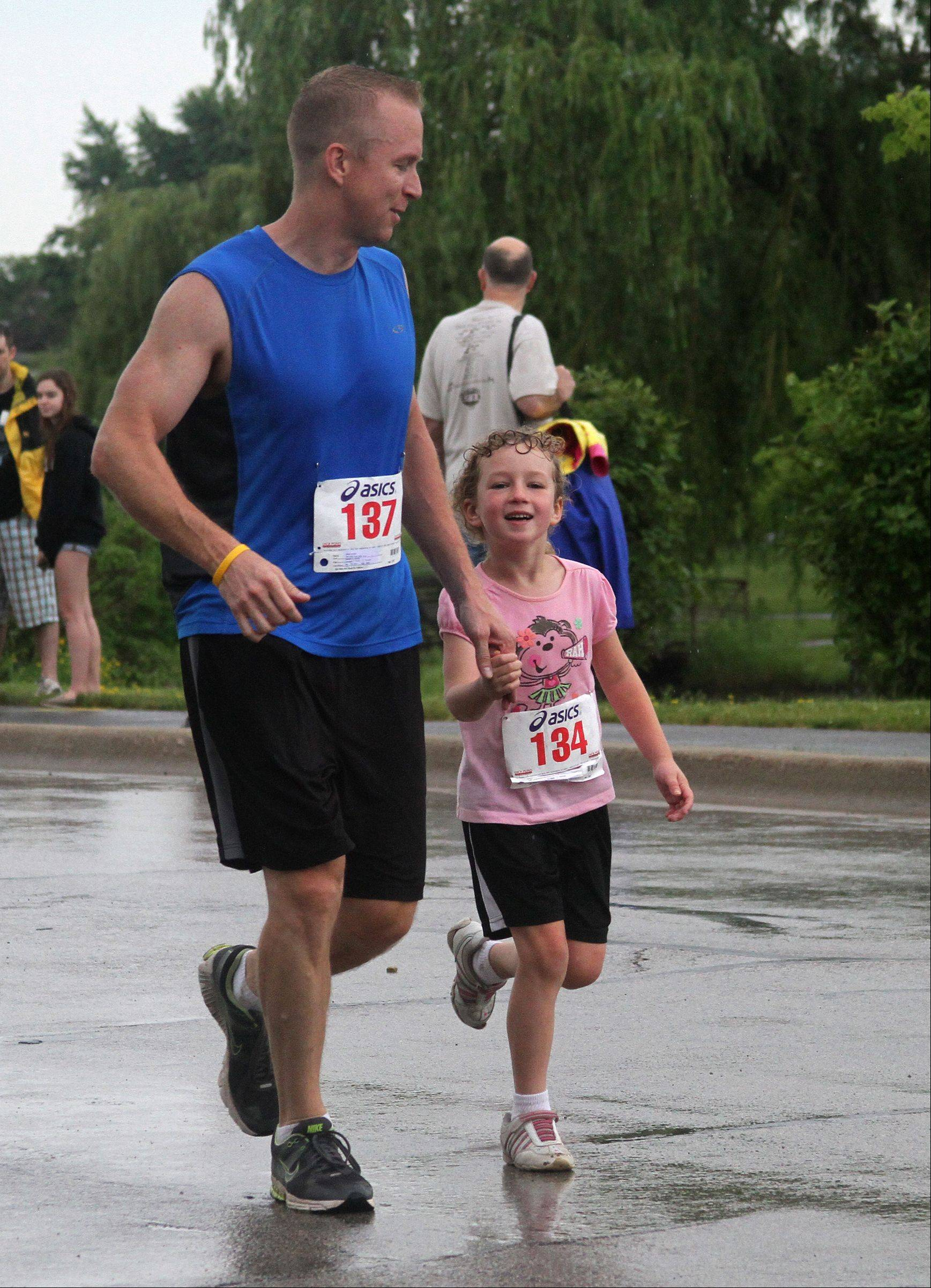 Steve and Chloe Curran of Bartlett run into the finish line at the 10th annual Bud�s Run 5K at the Ross Ferraro Town Center in Carol Stream on Saturday. The father-daughter pair ran the 5K together, along with the rest of their family. It was Chloe�s first 5K.