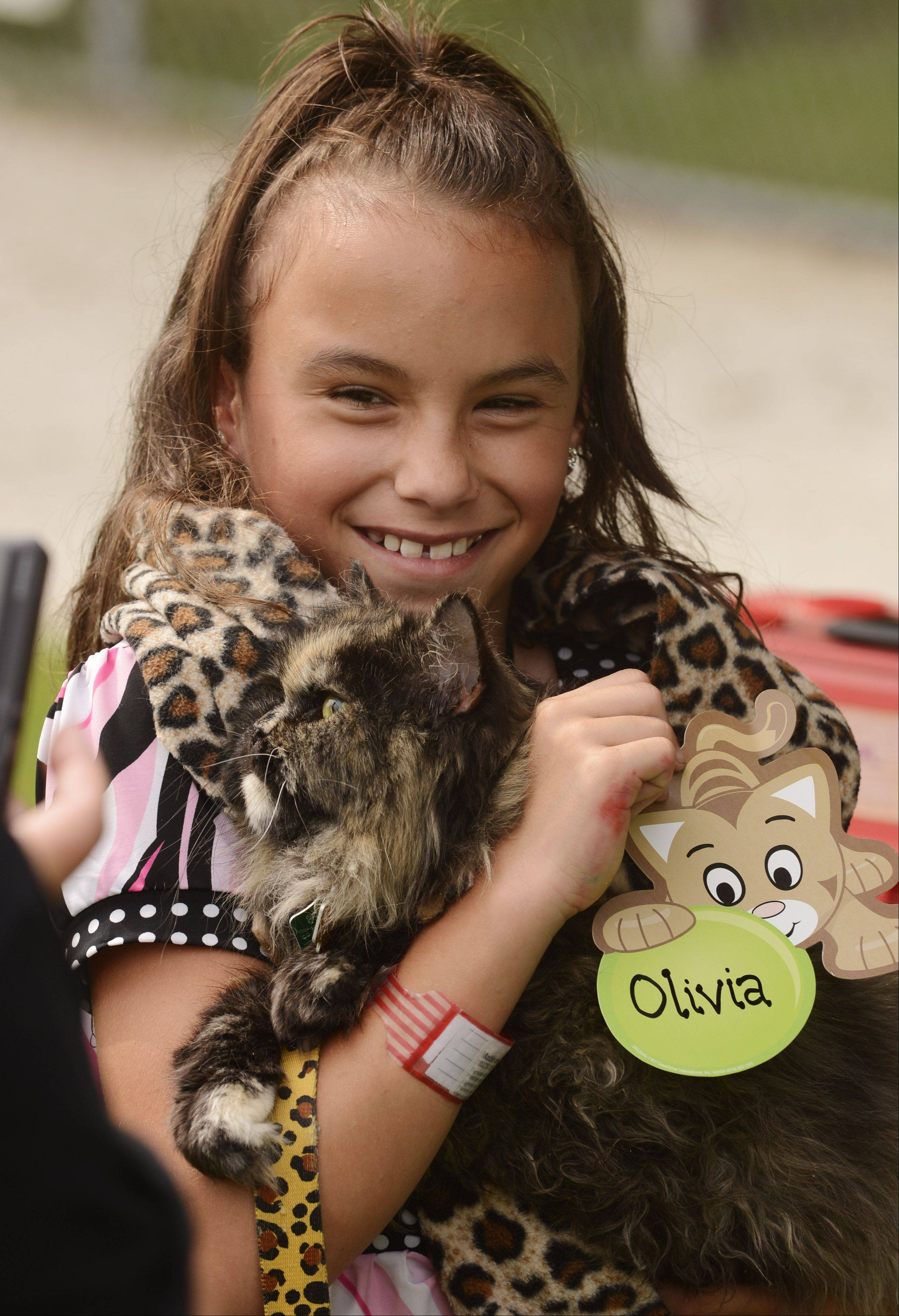 Mareena Mattison, 11, holds on to Olivia, her 13-year-old cat, prior to the start of the pet parade.