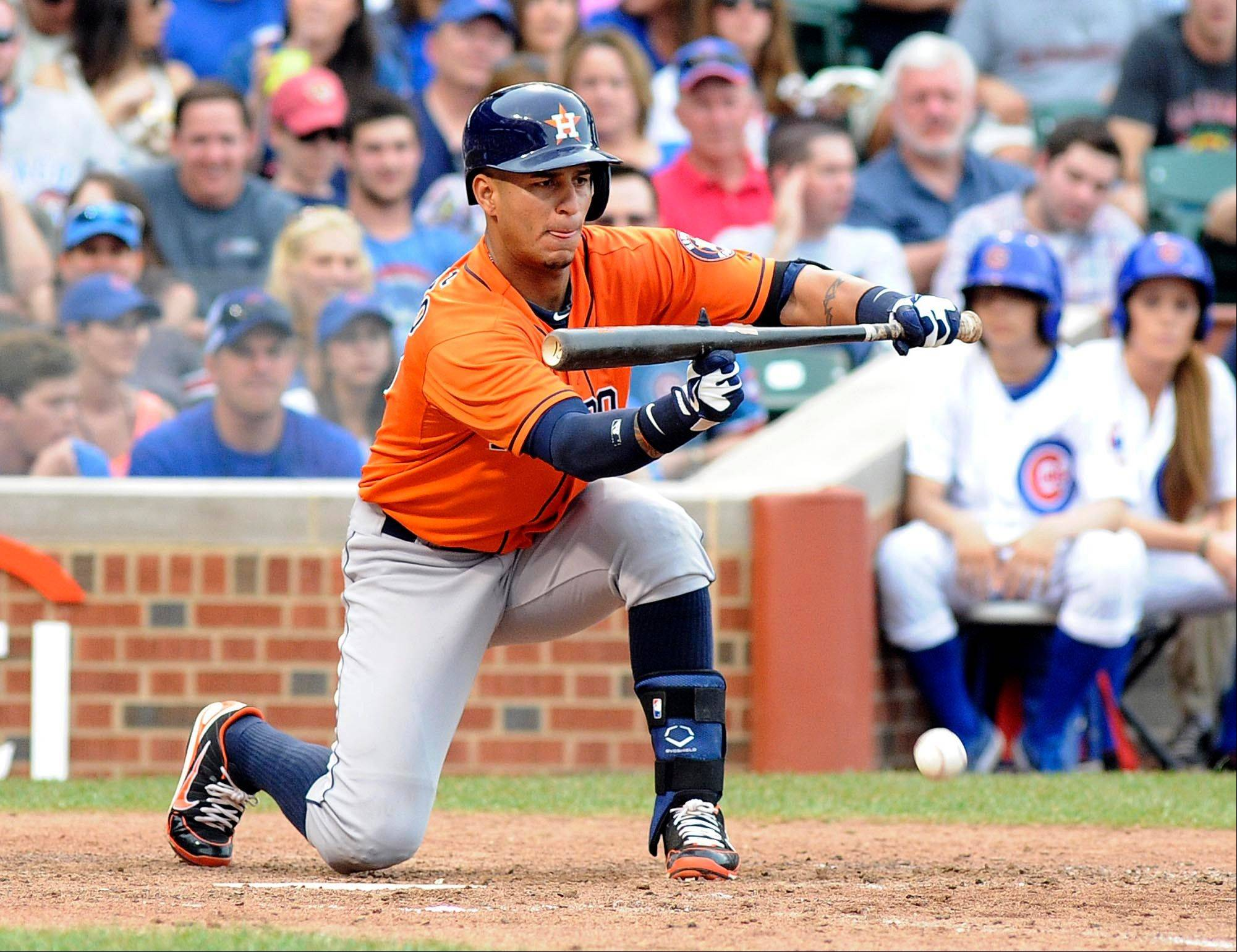 Houston Astros' Ronny Cedeno puts down a bunt, scoring the winning run, in the ninth inning of a baseball game against the Chicago Cubs, Saturday June 22, 2013, in Chicago, Ill. The Astros won 4-3. (AP photo/Joe Raymond)