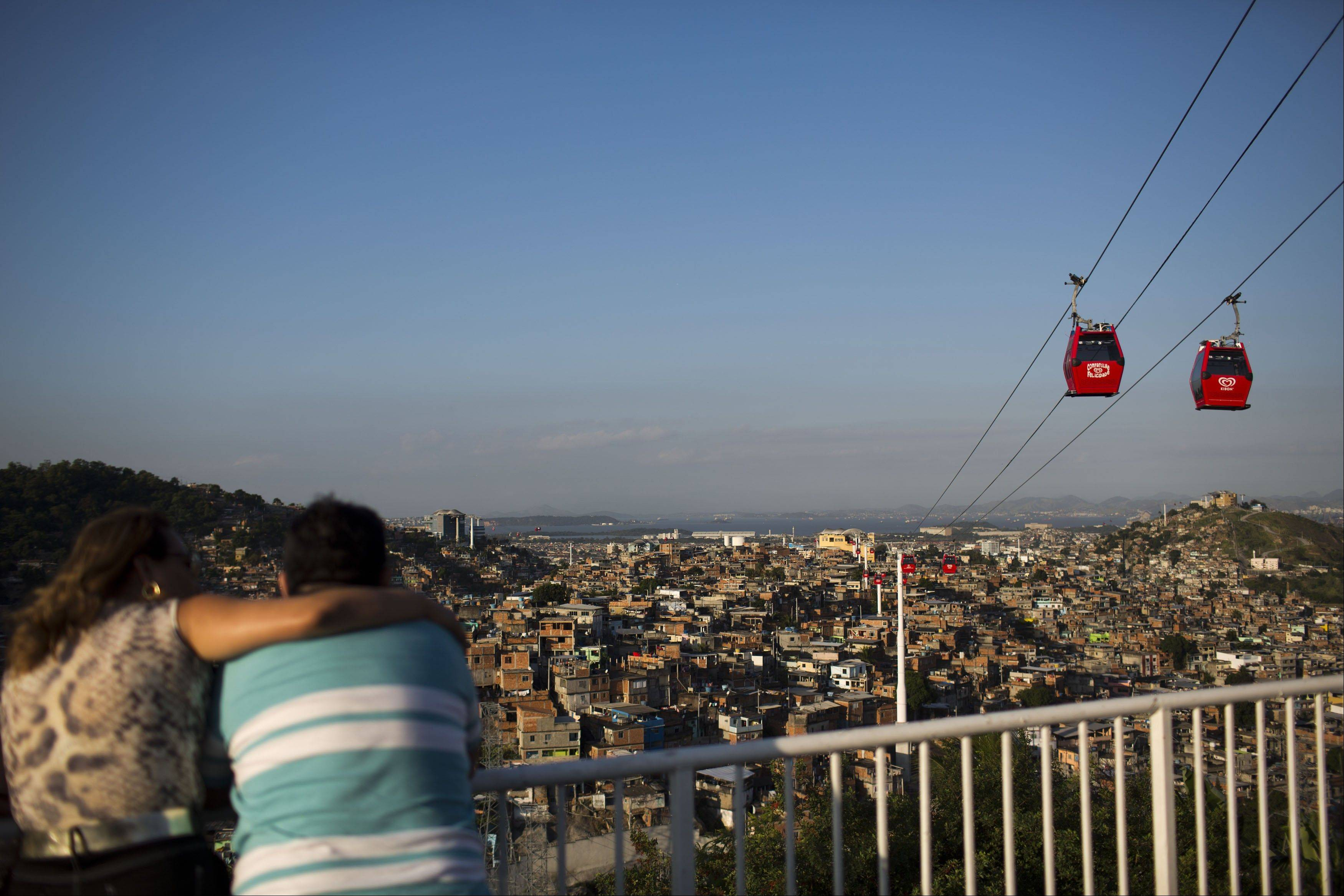 A couple looks out over the Complexo do Alemao slum where cable-cars move commuters above the homes in Rio de Janeiro, Brazil. The cable-car system linking six of Alemao's hilltops over a 2.3-mile route has become a popular tourist attraction.