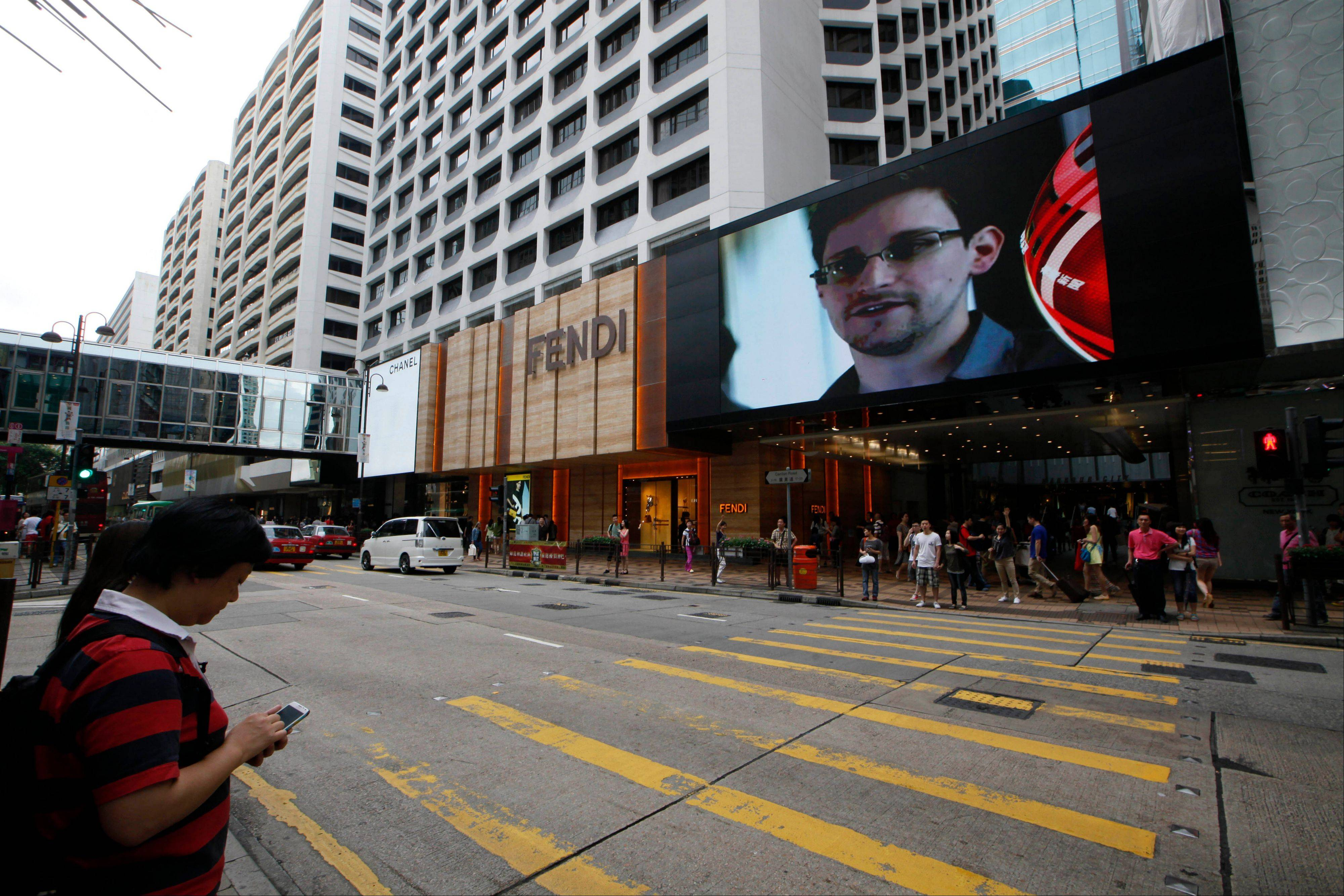 A TV screen shows a news report of Edward Snowden, a former CIA employee who leaked top-secret documents about sweeping U.S. surveillance programs, at a shopping mall Saturday in Hong Kong.