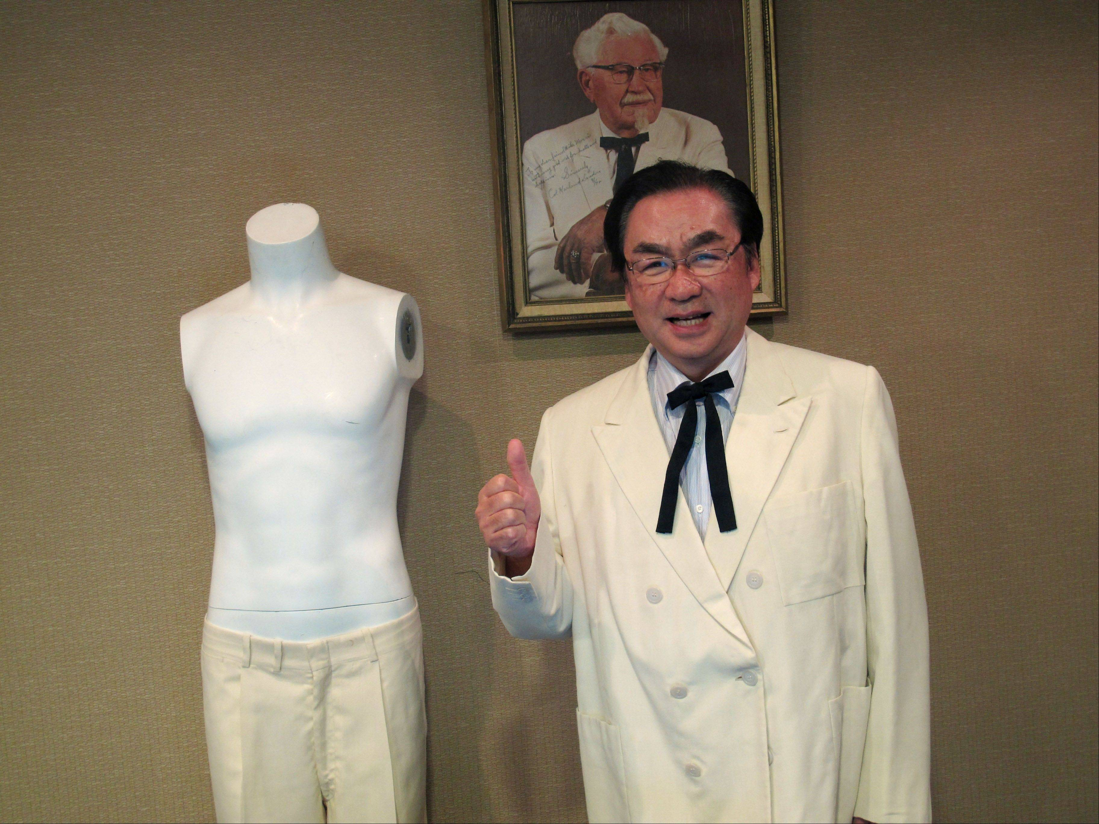 "Masao ""Charlie"" Watanabe, president and chief executive of Kentucky Fried Chicken Japan, stands Saturday beneath a portrait of company founder ""Colonel"" Harland Sanders, at Heritage Auctions in Dallas."