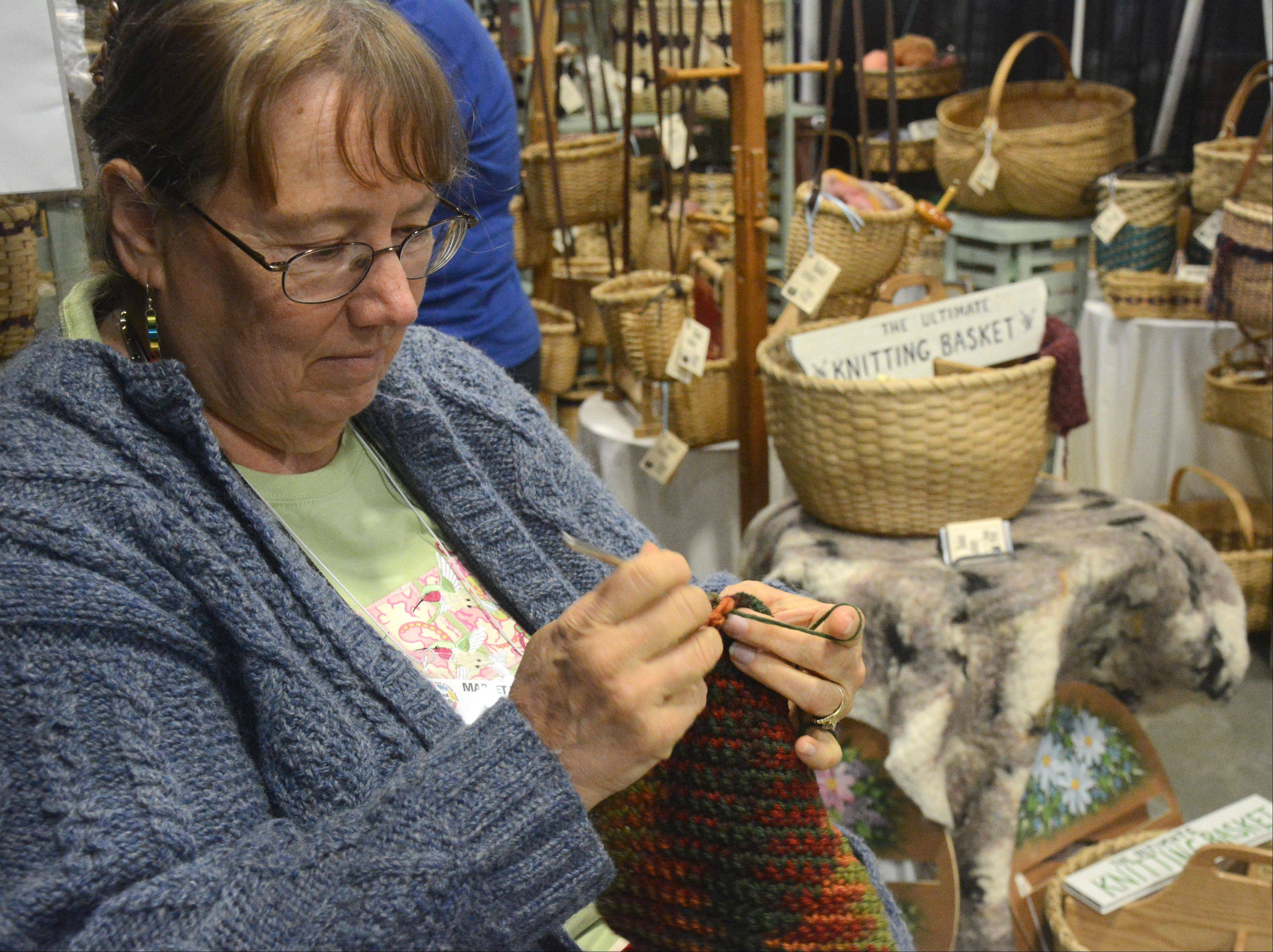 Susan Preuss of Waukesha, Wis., knits at her booth. She is a basket weaver by trade and was knitting an item to help display the knitting baskets she makes.