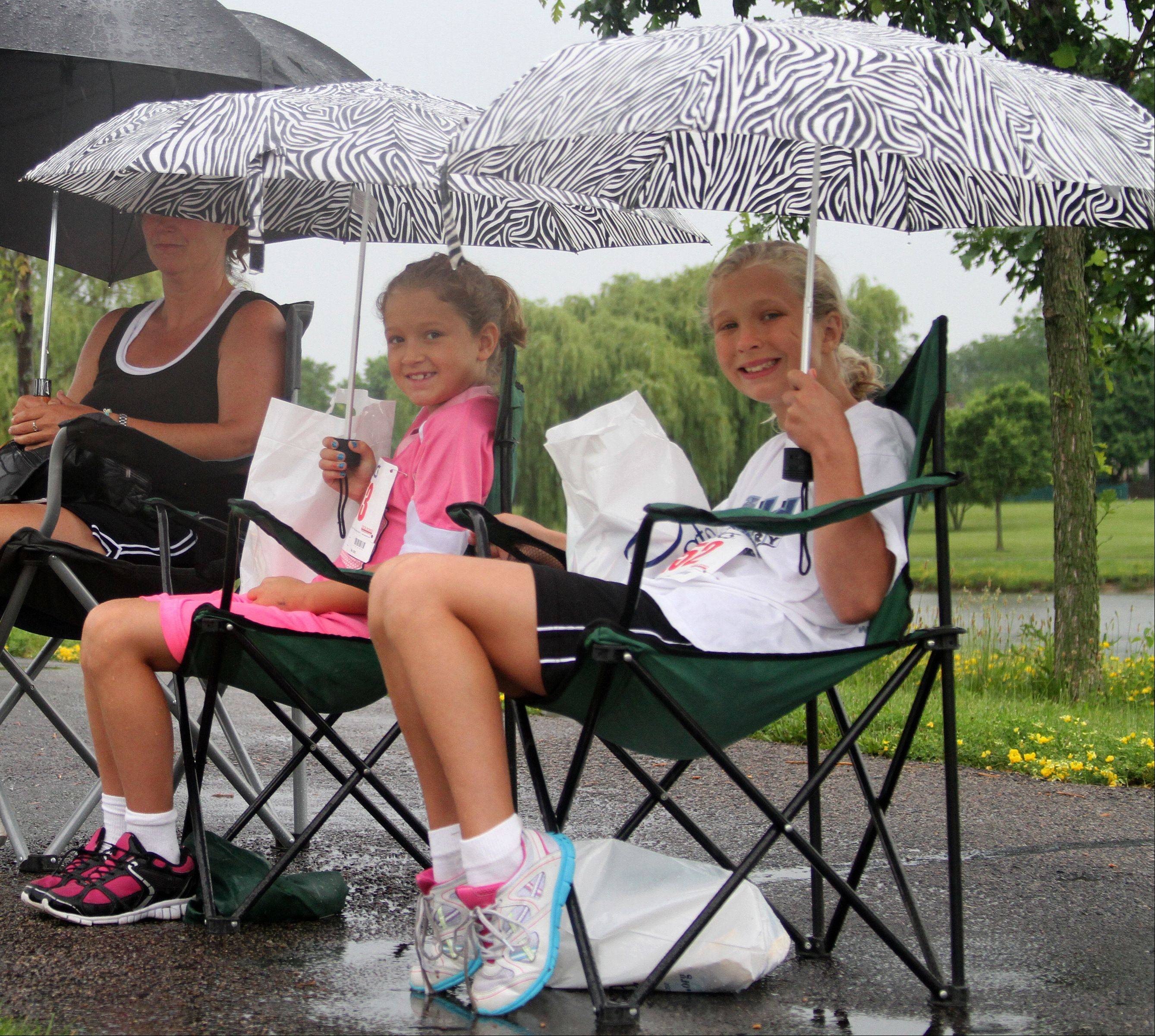 Brittany, 8, left, and Abby Miller, 10, wait in the rain for the 10th annual Bud's Run 5K to finish and the 1K to start at the Ross Ferraro Town Center in Carol Stream on Saturday.